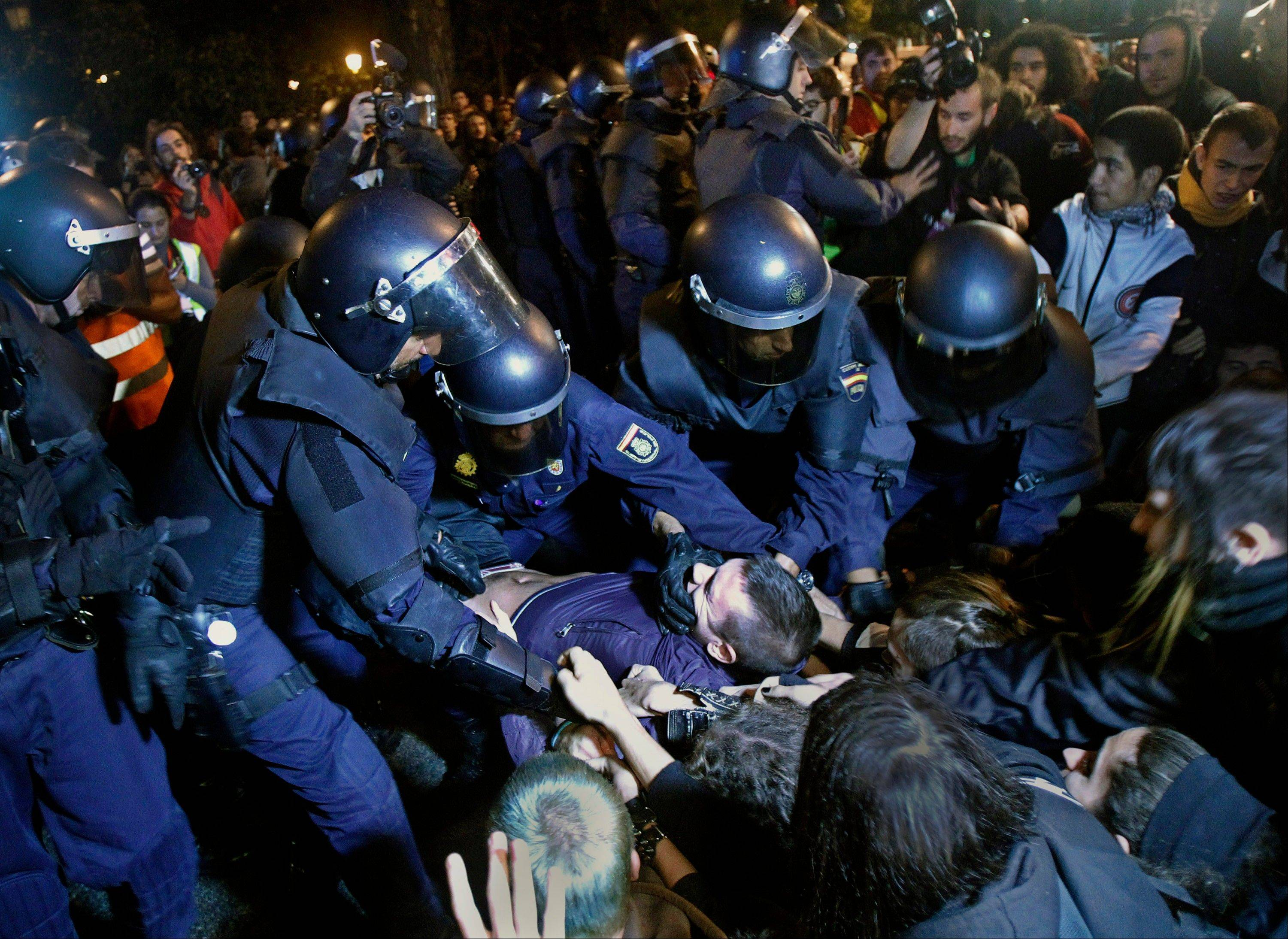 Police clash with protesters during a demonstration at the parliament against austerity measures announced by the Spanish government in Madrid, Spain, Wednesday.