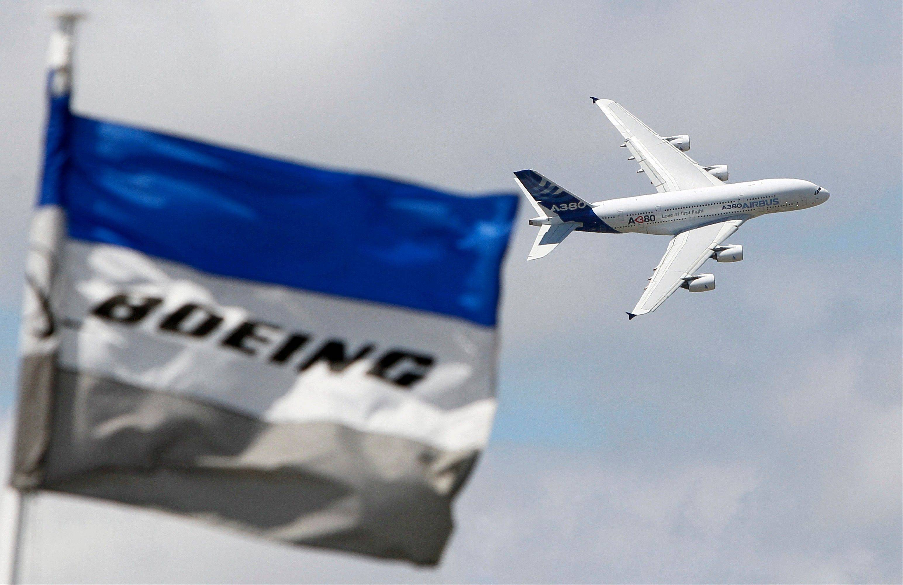 A Boeing flag flutters as an Airbus A380 flies past during a demonstration flight at the 49th Paris Air Show at Le Bourget airport, east of Paris.