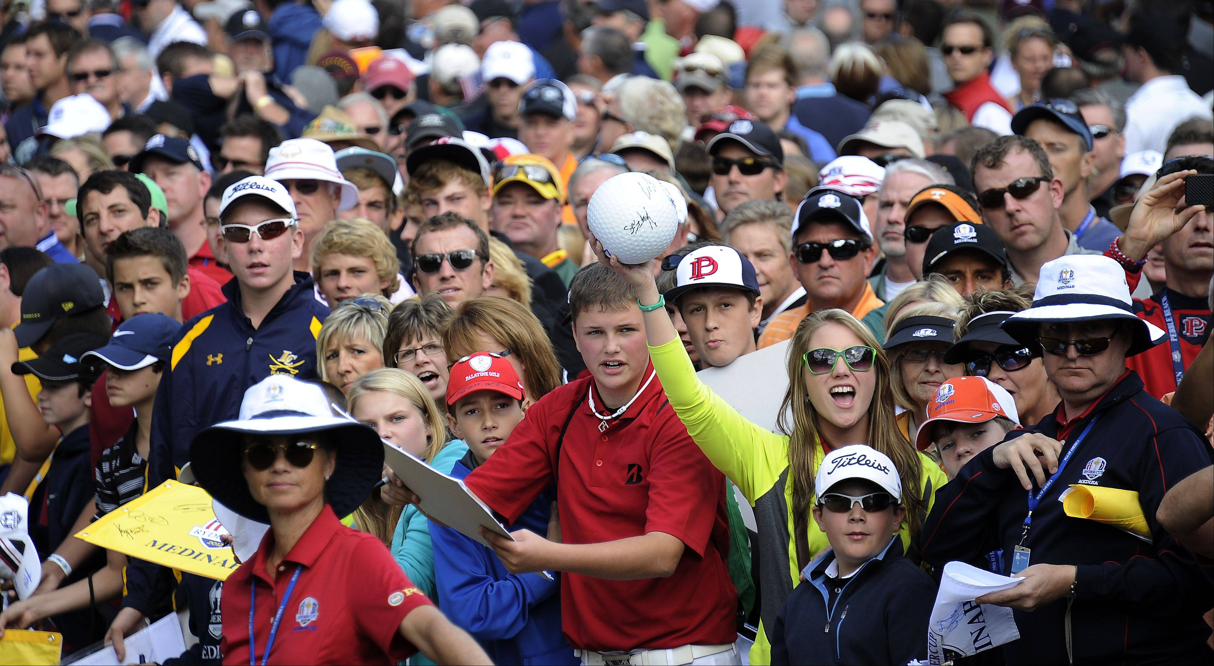 Screaming fans look to the golfers during the opening ceremonies of the Ryder Cup in Medinah on Thursday for autographs.