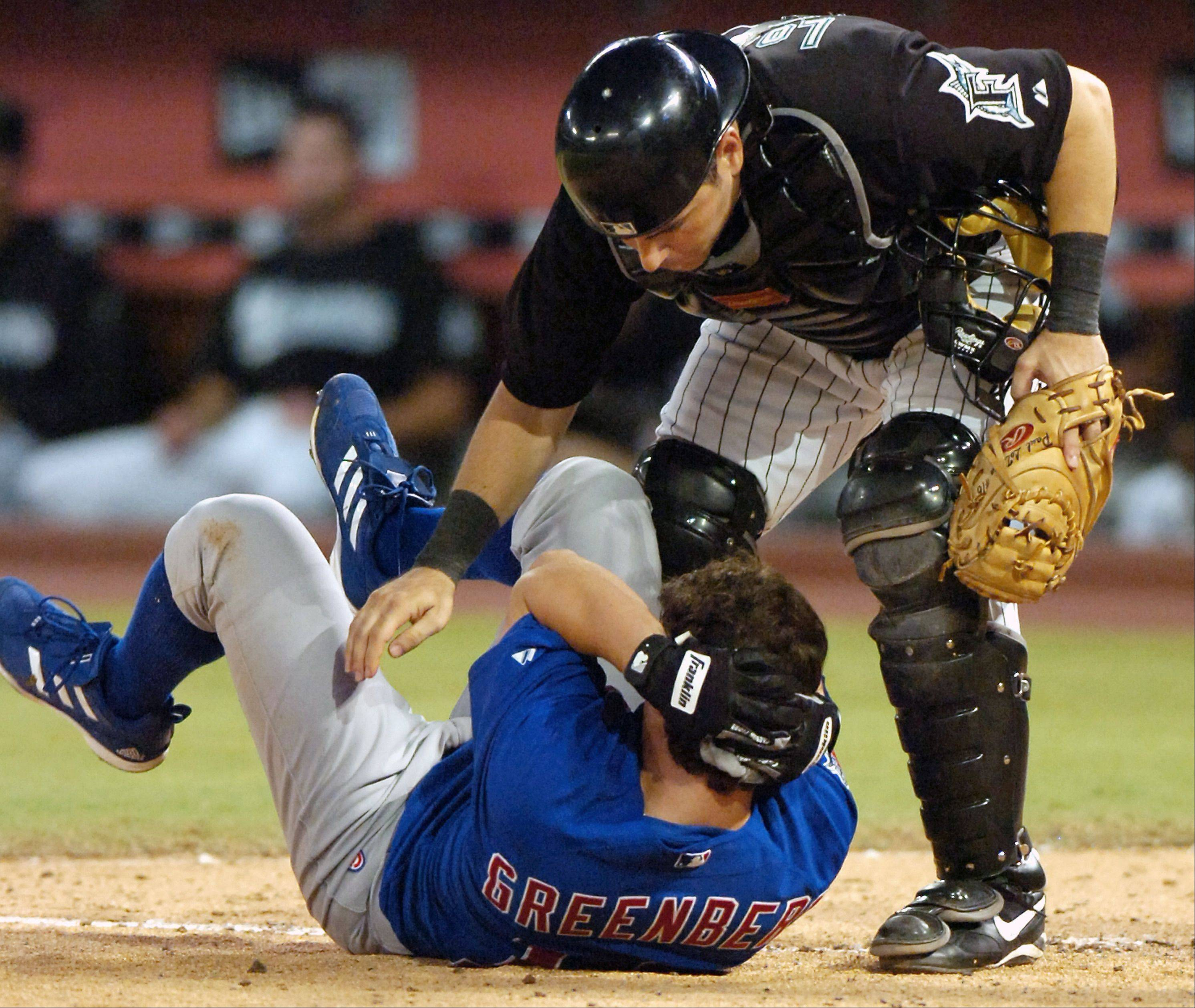 Florida Marlins catcher Paul Lo Duca rushes over to check on Chicago Cubs rookie Adam Greenberg after Greenberg was hit in the helmet by the first pitch he faced in the major leagues, from Florida Marlins relief pitcher Valerio Do Los Santos during the ninth inning, July 9, 2005, in Miami. The Cubs won 8-2.