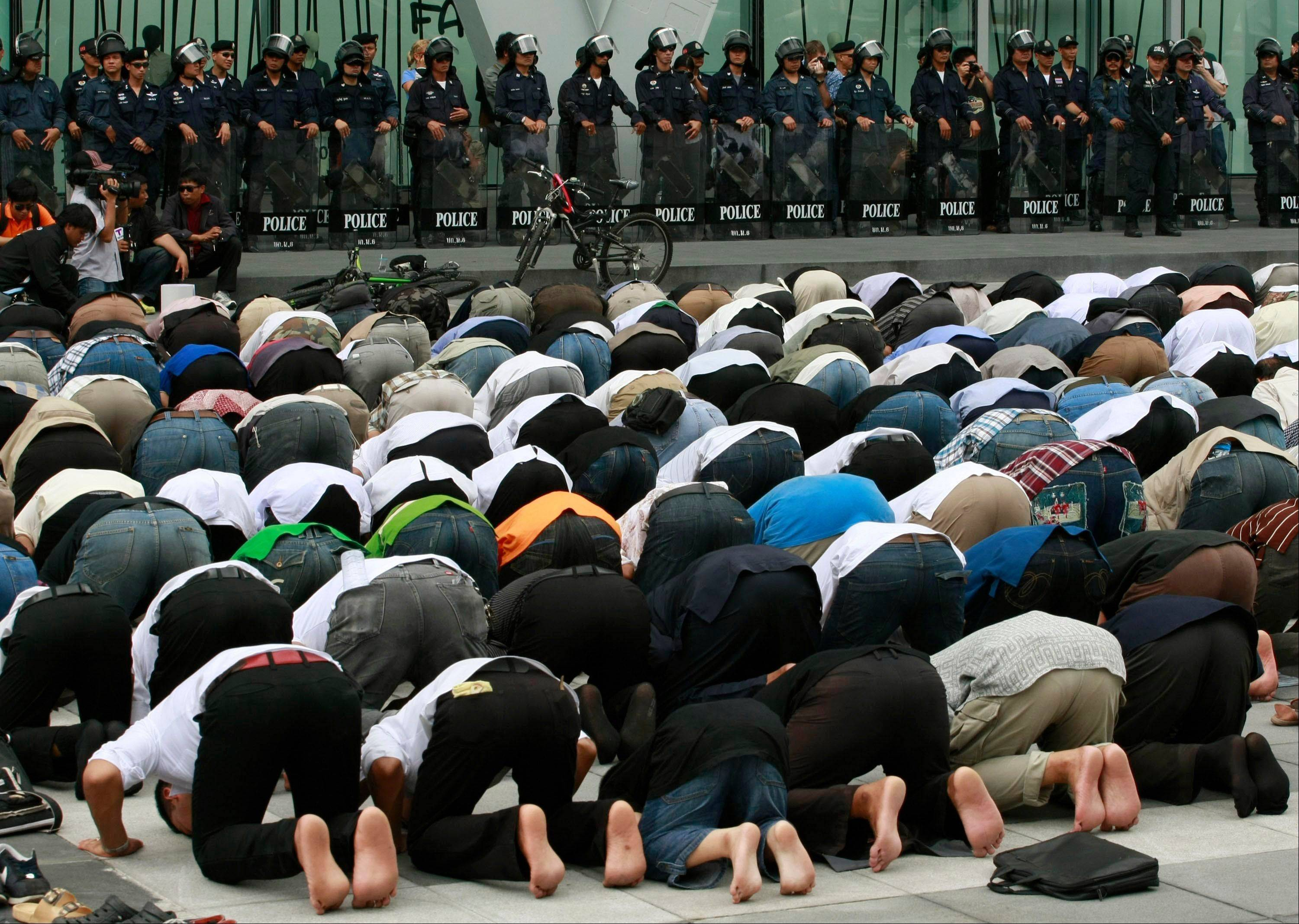 Thai police officers, background, look Thursday at Thai-Muslim demonstrators performing an afternoon pray outside a shopping mall where the office of Google Thailand is located. They were demonstrating against a video produced in the United States that denigrates the Prophet Muhammad.