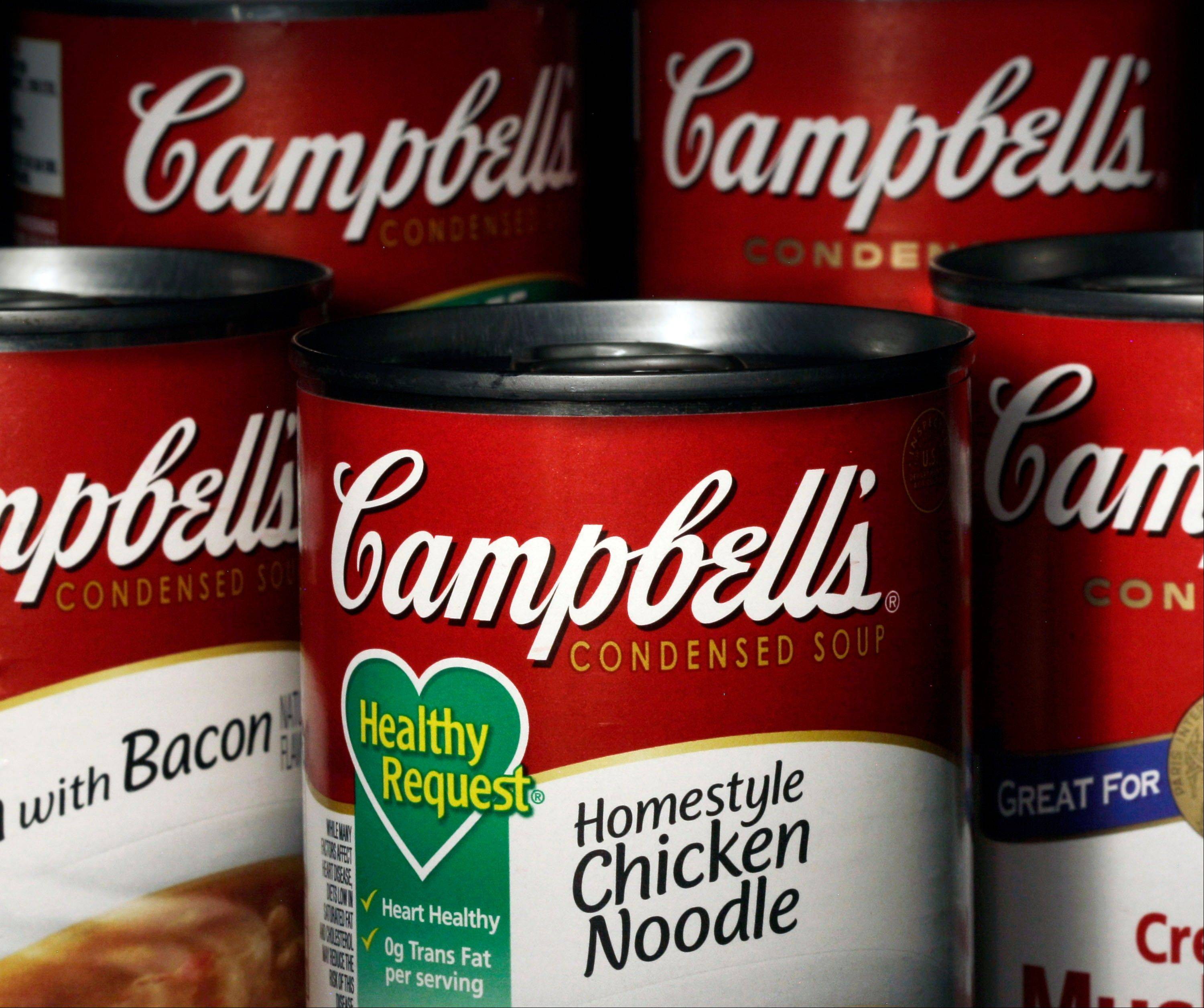 Campbell's soup cans sit on shelves in Moreland Hills, Ohio. Campbell announced Thursday that it will be closing two U.S. plants and cutting more than 700 jobs as it looks to trim costs amid declining canned soup consump
