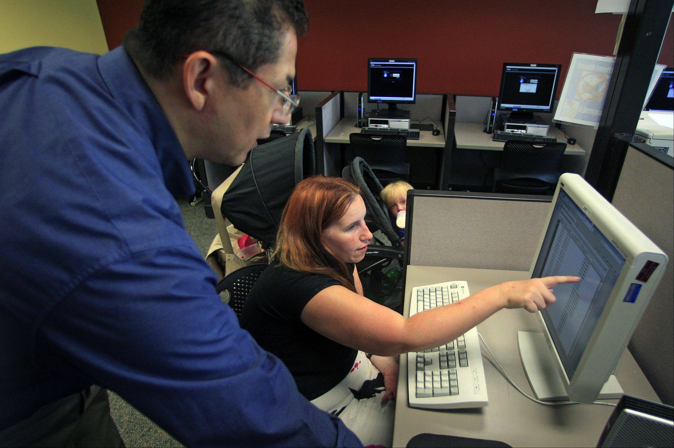 Associated Press/Sept. 21, 2012Deanna Aguilera, 30, of Salt Lake City, right, receives assistance from employment counselor Frank Trivino while job searching at Workforce Services, in Salt Lake City.