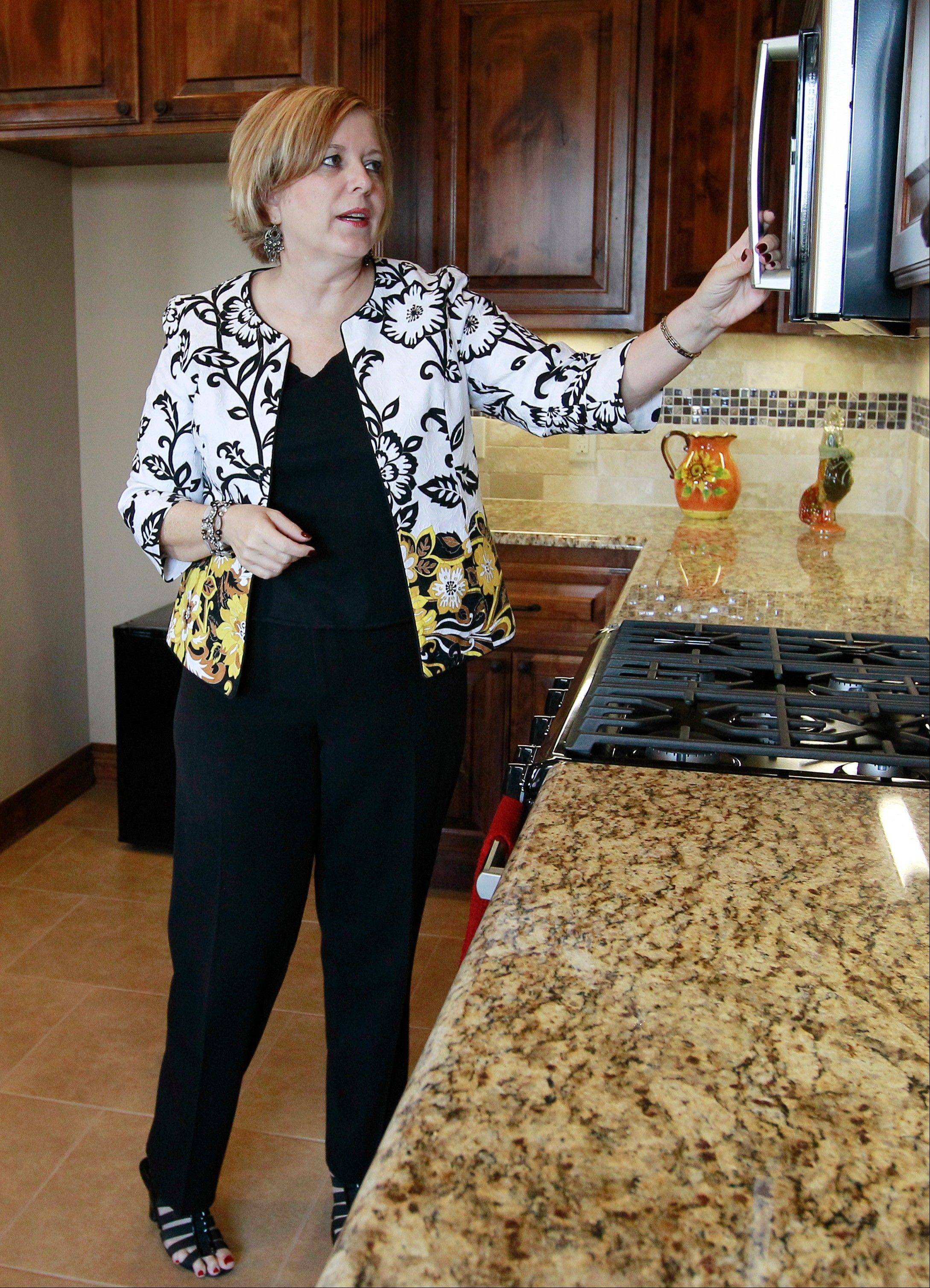 Associated Press/Sept. 21, 2012Realtor Kimi George tours the kitchen of a home for sale in Oklahoma City. Average U.S. rates on fixed mortgages fell again to new record lows.