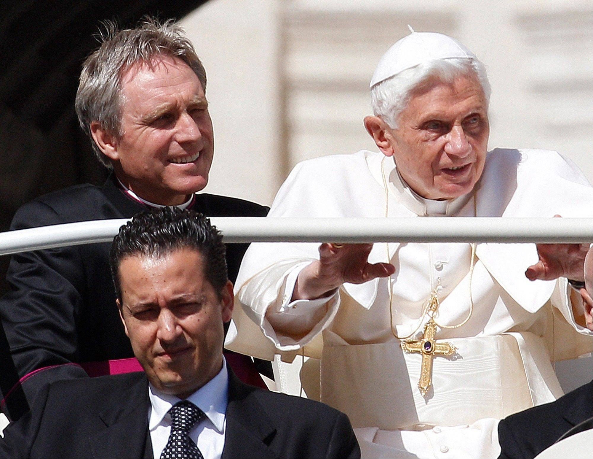 In this file photo, Pope Benedict XVI arrives in St. Peter's square as his then-butler Paolo Gabriele, bottom, and his personal secretary Georg Gaenswein sit in the car with him. Pope Benedict XVI's ex-butler Paolo Gabriele and another Vatican lay employee, Claudio Sciarpelletti, are scheduled to go on trial Saturday, Sept. 29, 2012, in the embarrassing theft of papal documents that exposed alleged corruption at the Holy See's highest levels.