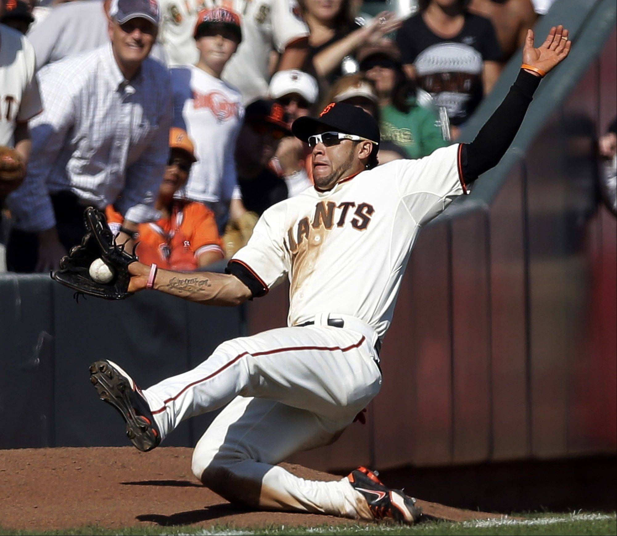 Giants left fielder Gregor Blanco makes a sliding catch on a pop fly by the Diamondbacks' Adam Eaton during the ninth inning Thursday in San Francisco.