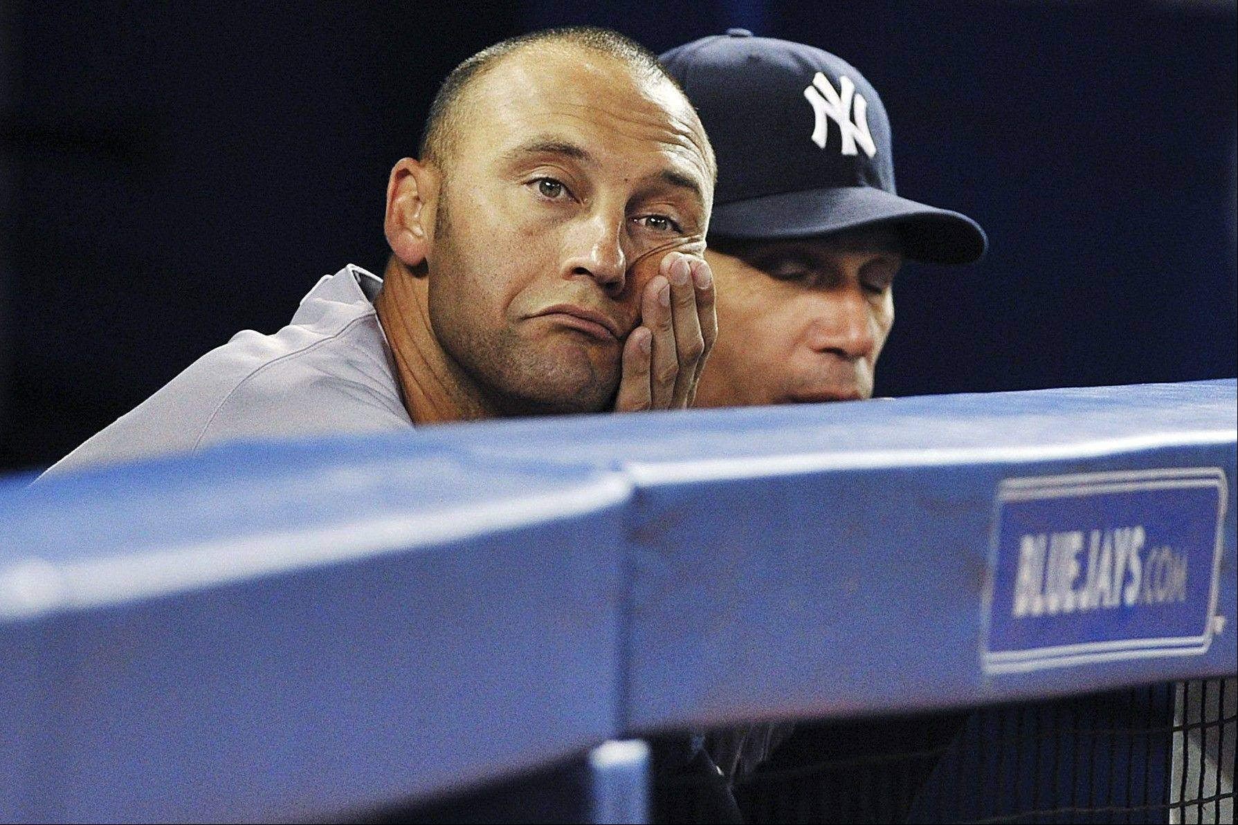 The Yankees' Derek Jeter sits dejectedly in the dugout alongside manager Joe Girardi, right, during the ninth inning of a 6-0 loss in Toronto.