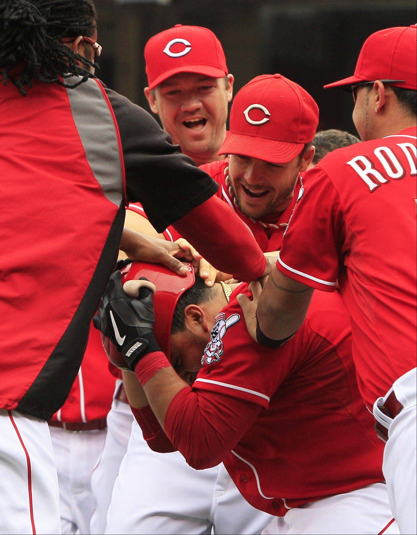 Cincinnati's Dioner Navarro, bottom, covers his head as he is mobbed by his teammates after hitting a triple to drive in the winning run Thursday at home against the Milwaukee Brewers.