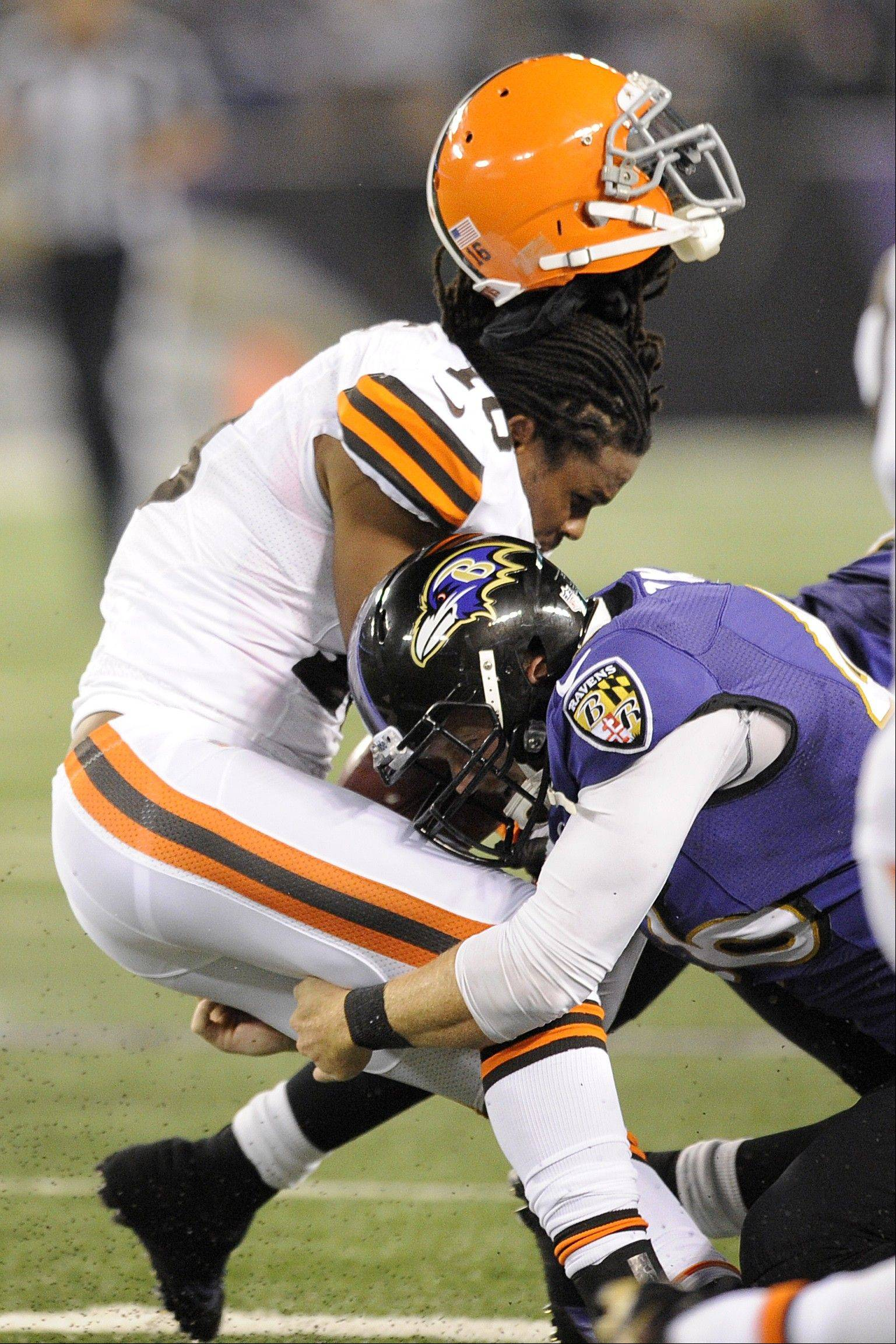 Ravens long snapper Morgan Cox tackles Cleveland Browns wide receiver Josh Cribbs as Cribbs' helmet is dislodged from a hit by another player Thursday night in Baltimore.