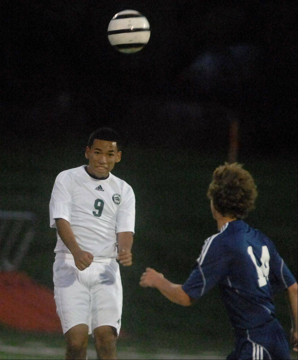 Shawn Herrera of Glenbard West heads the ball over Adam Jones of Bartlett during the Bartlett at Glenbard West boys soccer game Thursday.