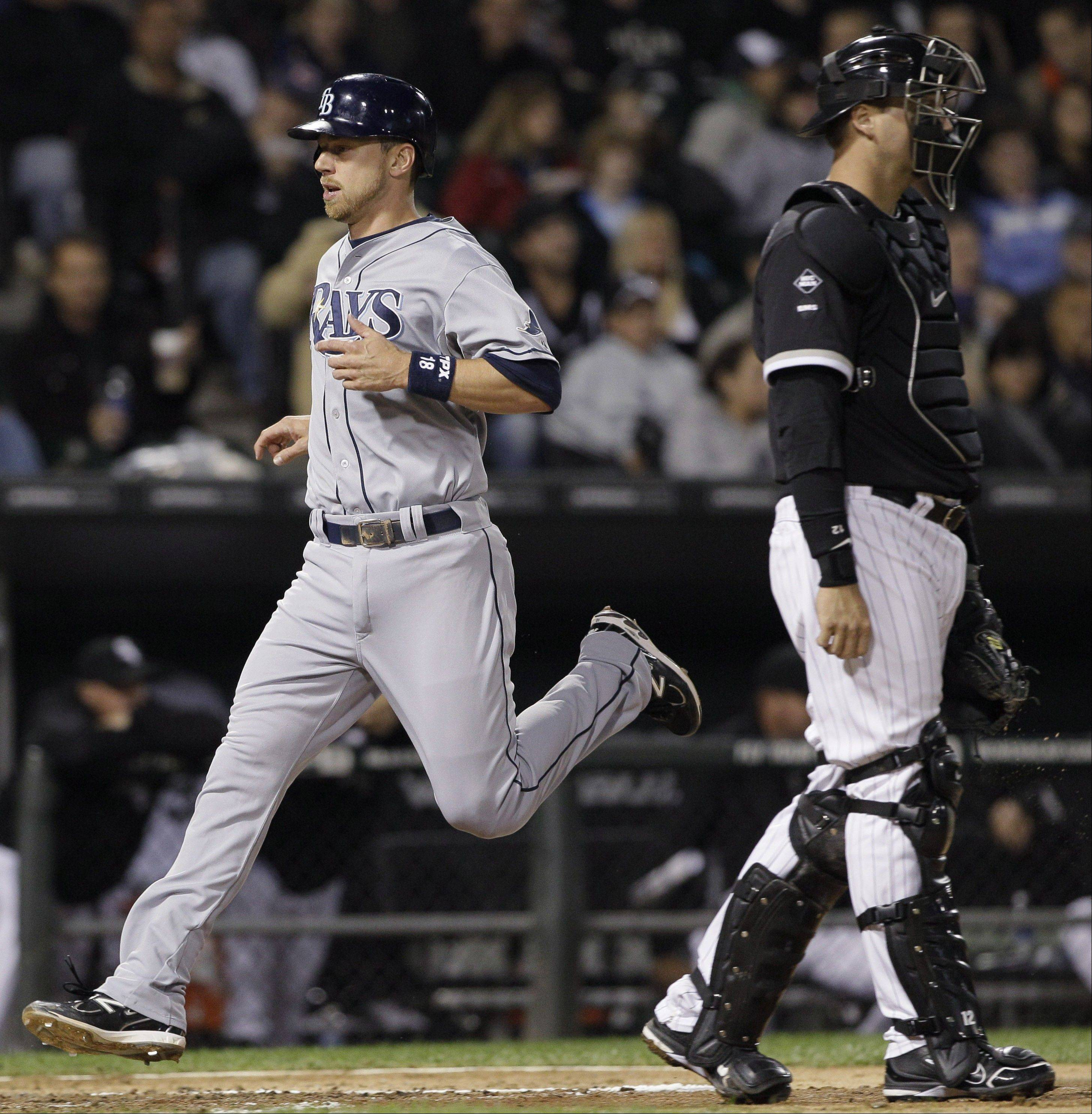 Tampa Bay Rays' Ben Zobrist, left, scores on a sacrifice fly hit by Carlos Pena as White Sox catcher A.J. Pierzynski looks to the field during the fourth inning Thursday night at U.S. Cellular Field.