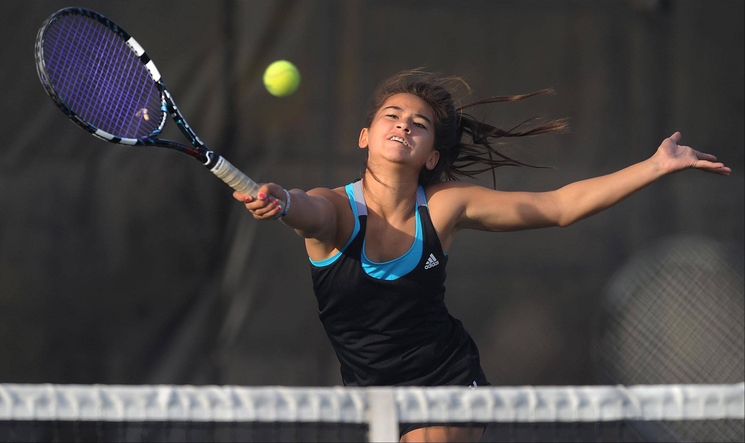Batavia's Amelia Cogan stretches to return a forehand at the net as she and partner Jenny Mizikar defeated St. Charles East's Kelsie Roberton and Haydyn Jones at No. 1 doubles Thursday in St. Charles.
