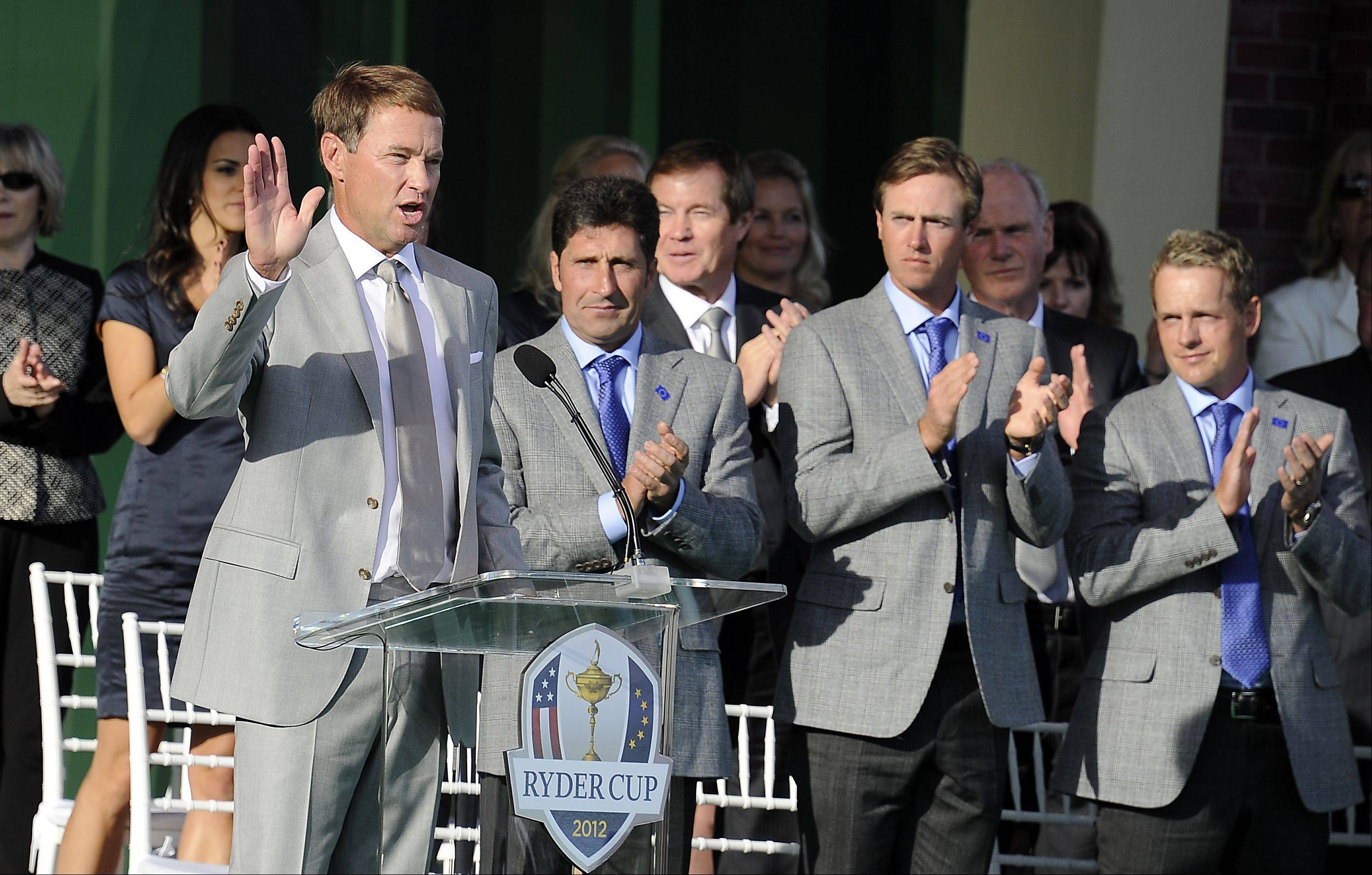 Davis Love III, captain of Team USA, speaks to the large crowd as Team Europe's captain Jose Maria Olazabal looks on with other members of the European team.