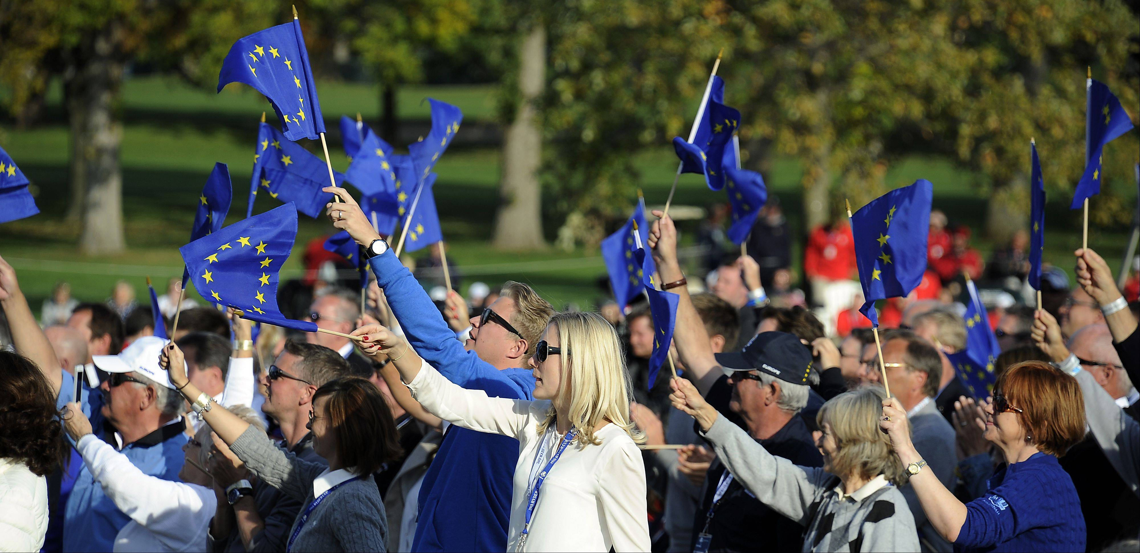 Team Europe's fans cheer and wave flags.