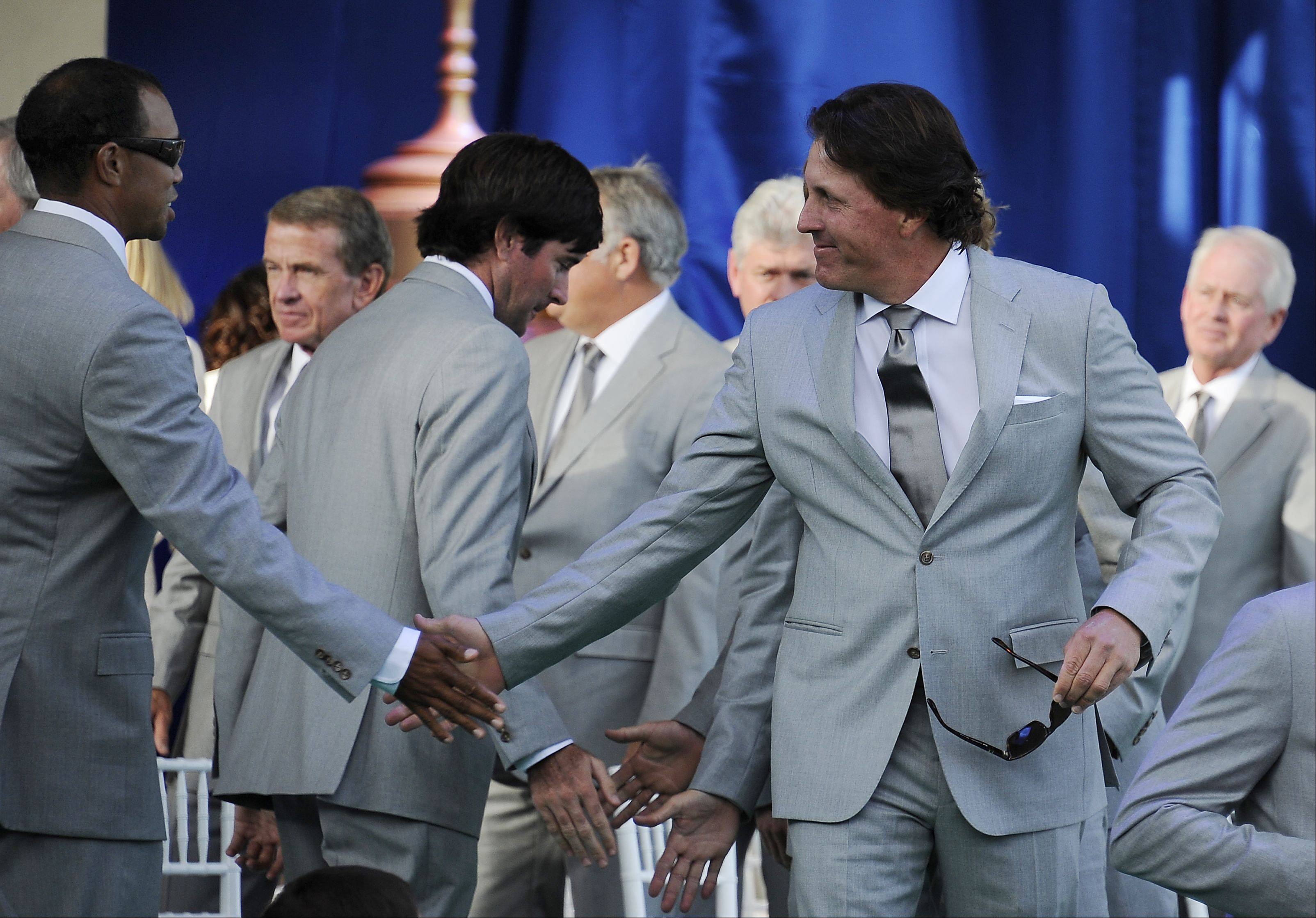 United States team member Phil Mickelson shakes hands with teammate Tiger Woods.