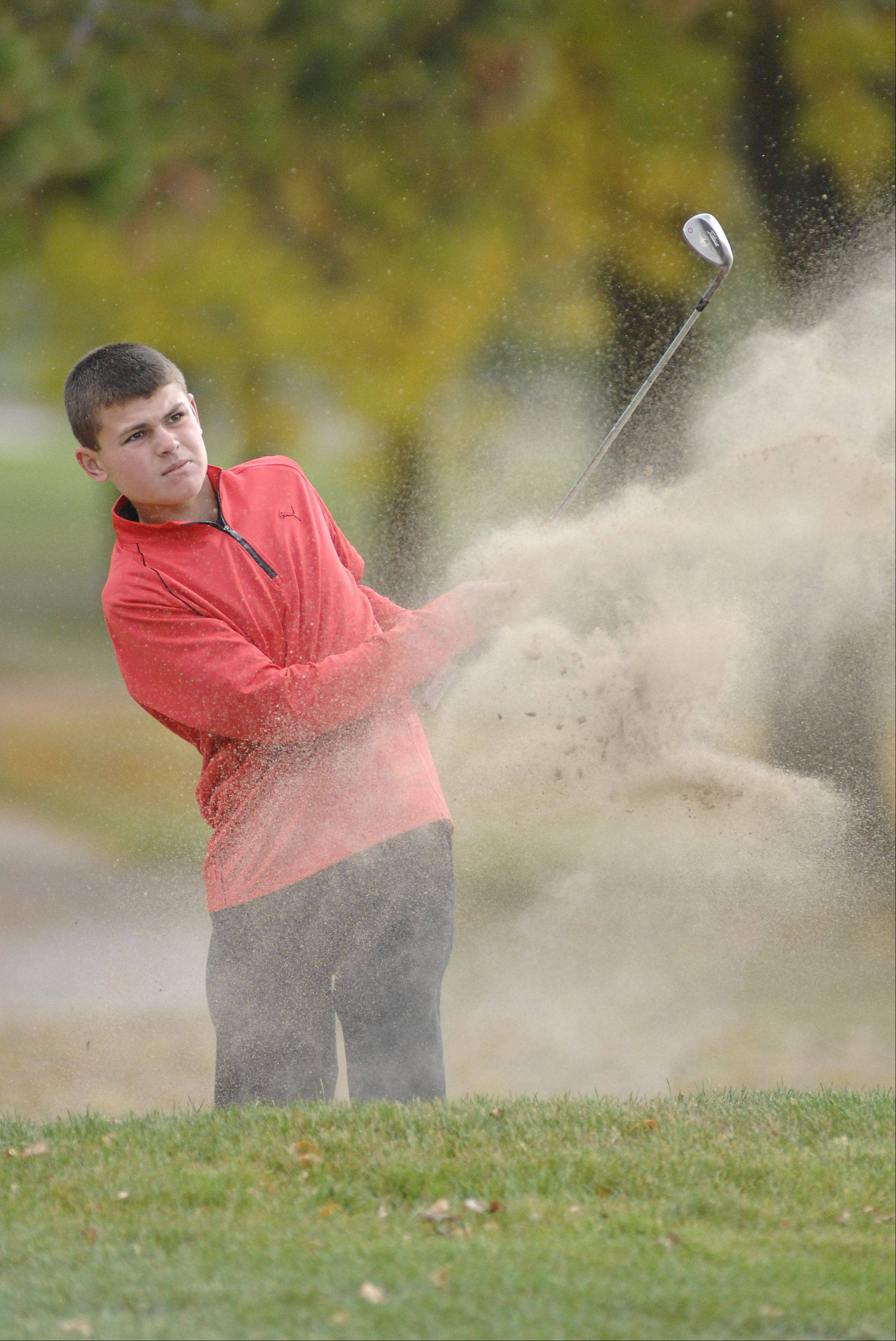 Huntley's Trent Craig blasts out of a sand trap on the sixth hole in the Fox Valley Conference tournament at Crystal Woods Golf Course in Woodstock on Thursday, September 27.
