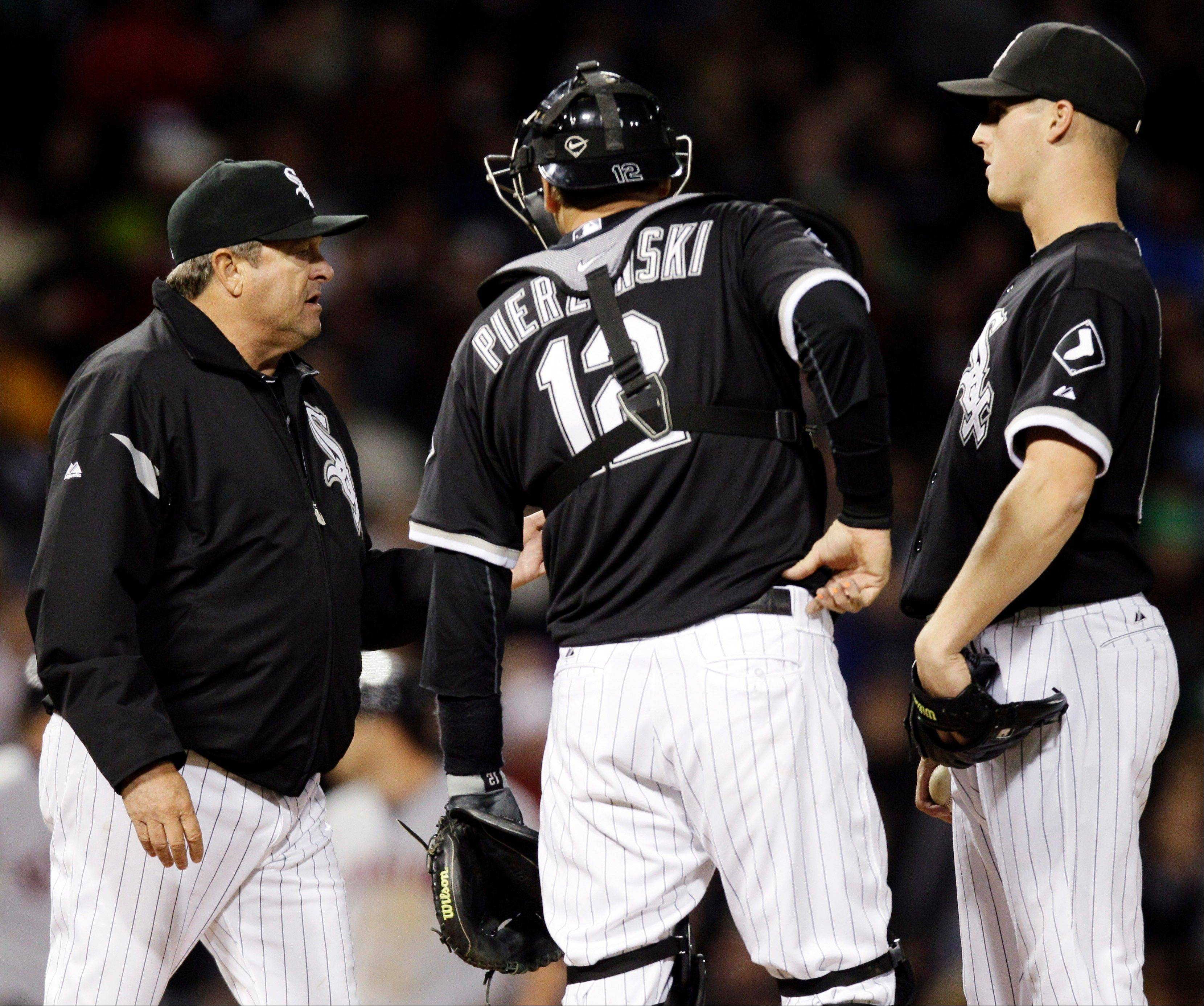 White Sox pitching coach Don Cooper, left, talks with catcher A.J. Pierzynski, center, and relief pitcher Nate Jones Wednesday during the sixth inning against the Cleveland Indians.