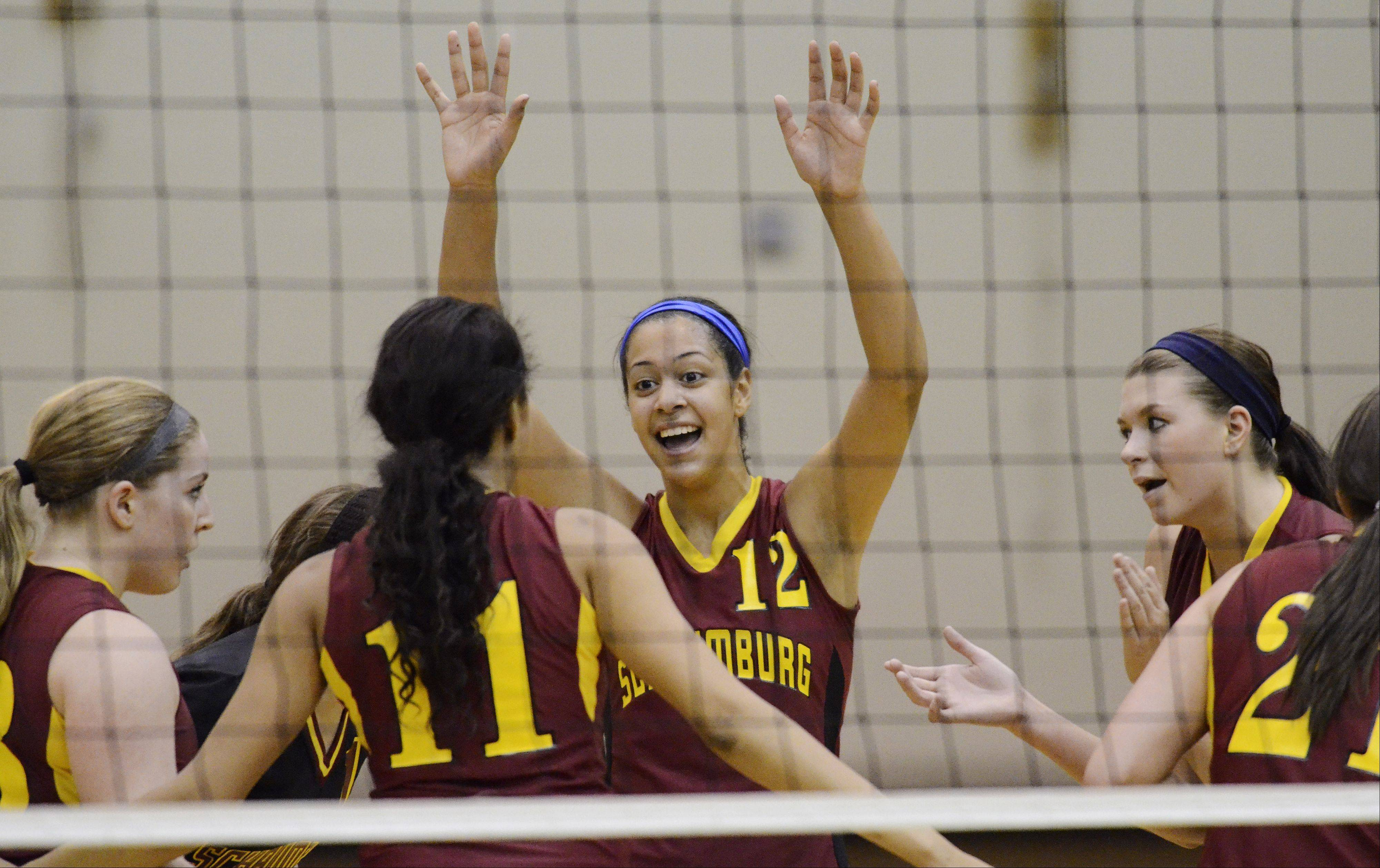 Schaumburg's Kiana Lewis, center, celebrates with her teammates as the Saxons close in on a victory against Barrington.