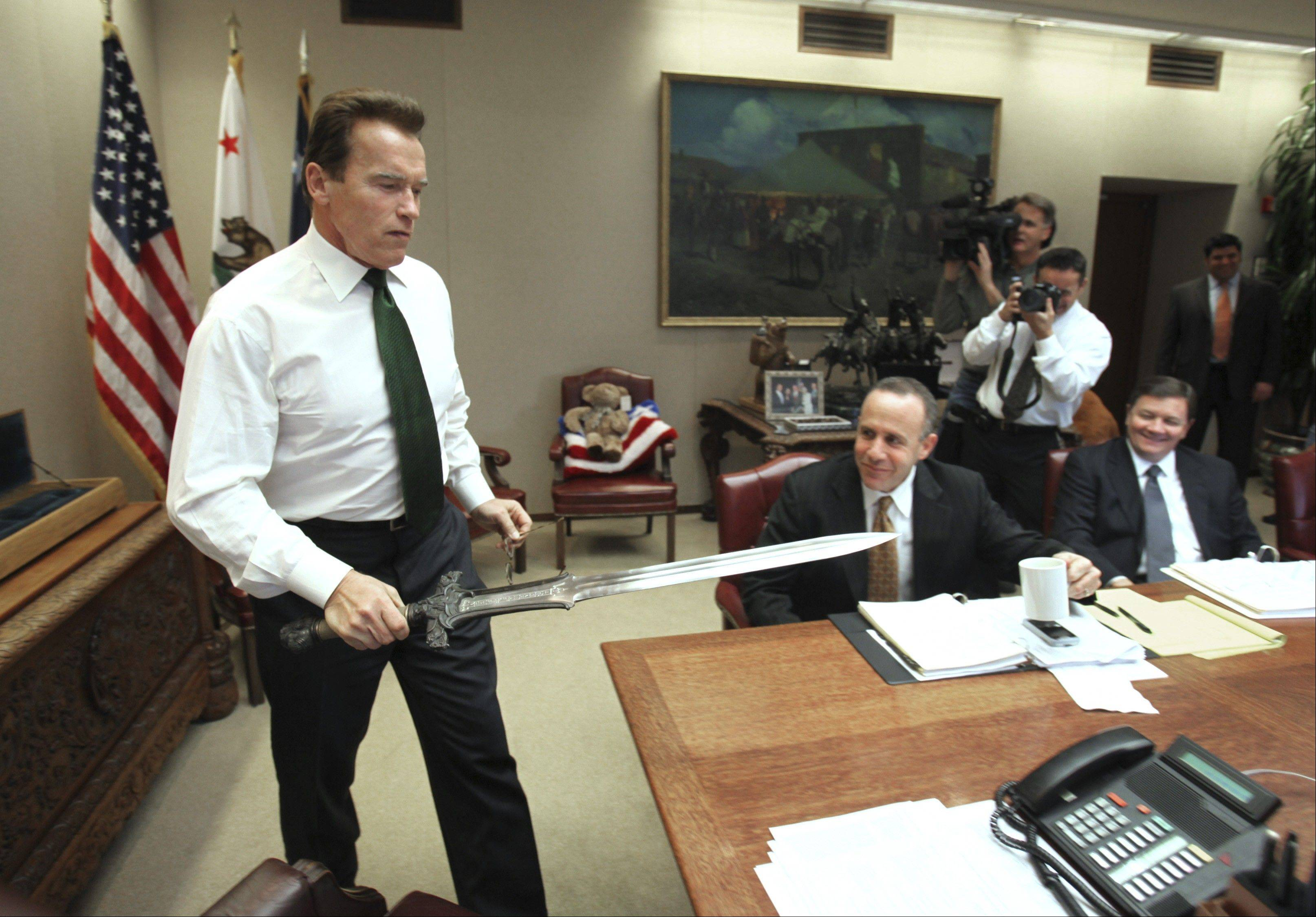 Associated Press/Jan. 13, 2009 Gov. Arnold Schwarzenegger brings the sword he used in the movie �Conan The Barbarian,� to the conference table before the start of budget negotiations with legislative leaders at the Capitol in Sacramento, Calif.
