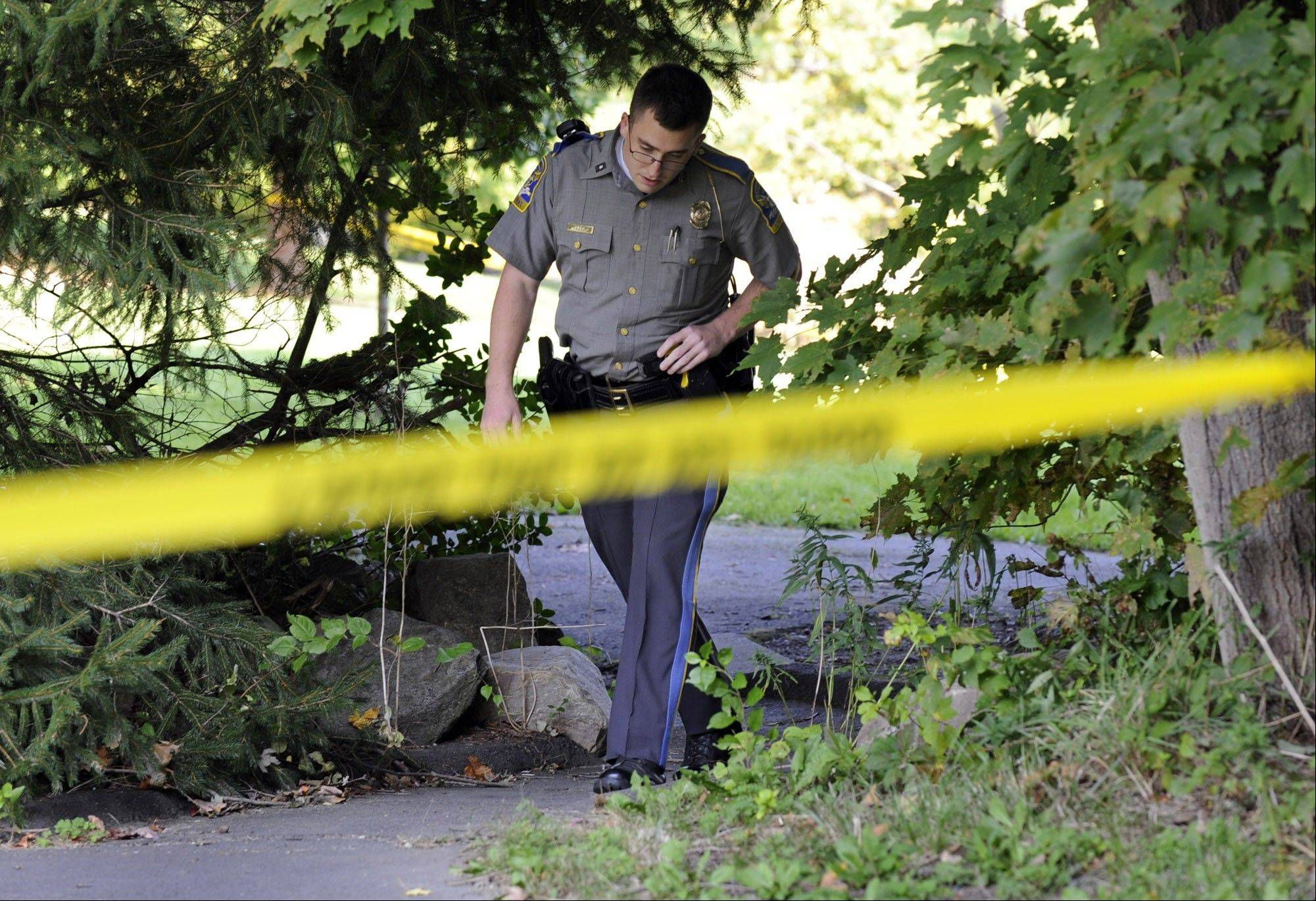 State Trooper Matt Losh emerges from the backyard of a home on Meeting House Hill Circle in New Fairfield, Conn., where a fatal shooting took place, Thursday, Sept. 27, 2012. A Connecticut man fatally shot a masked teenager in self-defense during what appeared to be an attempted burglary early Thursday morning, then discovered that he had killed his son, state police said. (