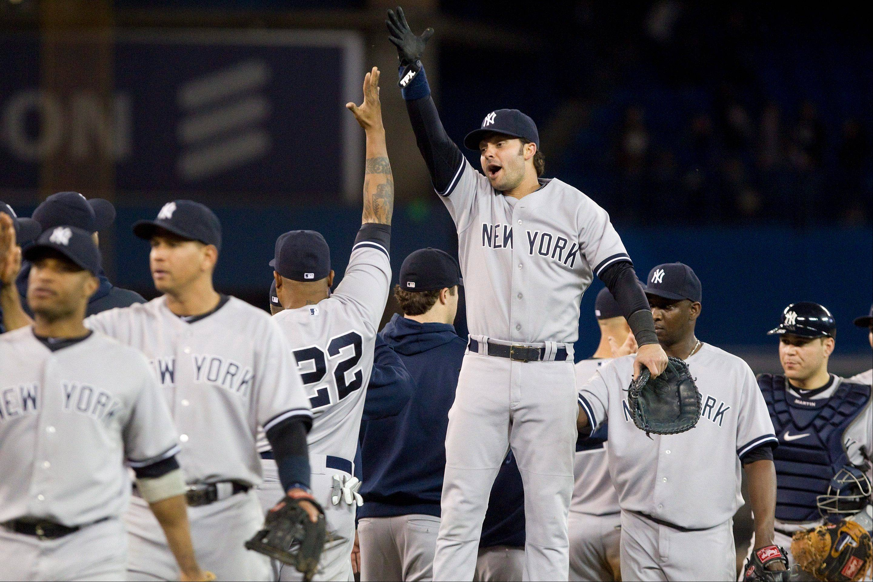 Nick Swisher high-fives Andruw Jones (22) as they celebrate the Yankees� 11-4 win over the Blue Jays Friday in Toronto.