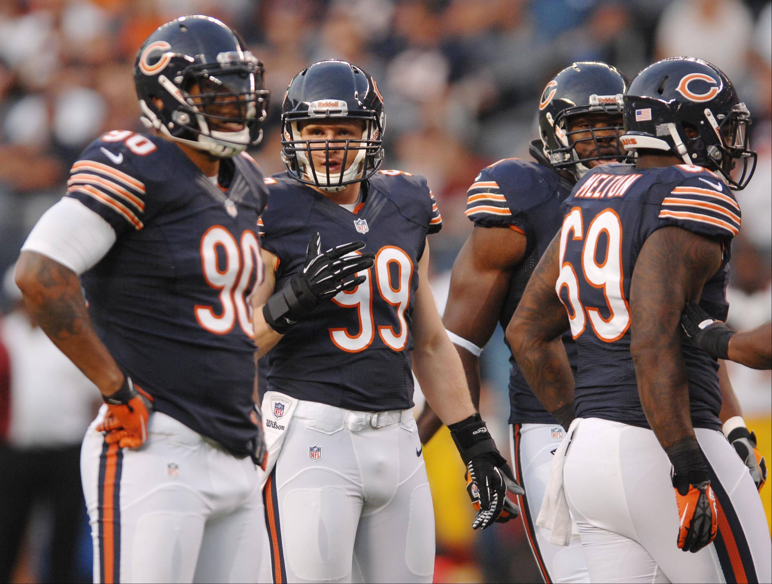 Bears defensive end Shea McClellin gets some advice from all-pro standout Julius Peppers.