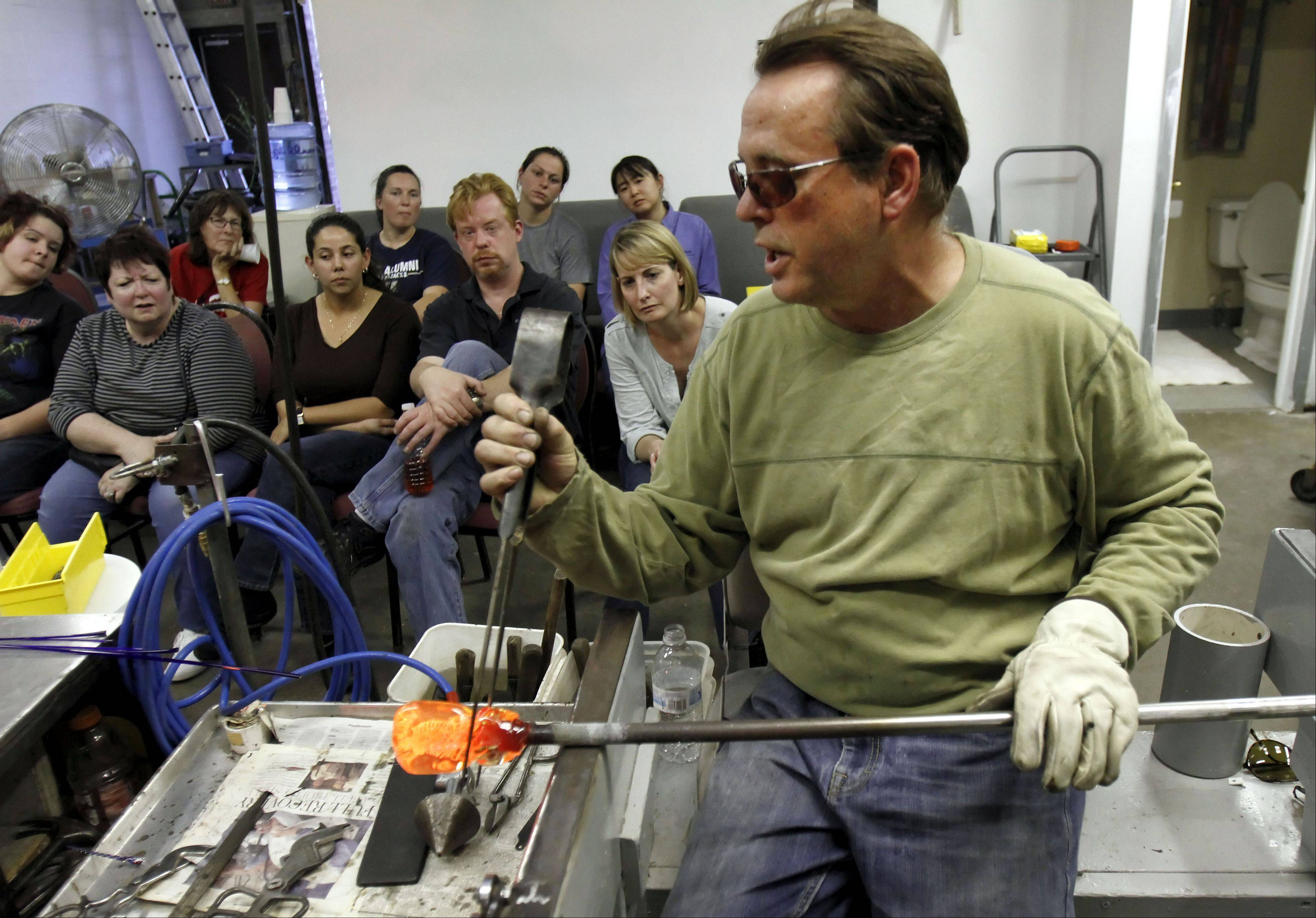 Glass artist Peter Patterson works with hot glass during a class at his workshop in Mundelein.