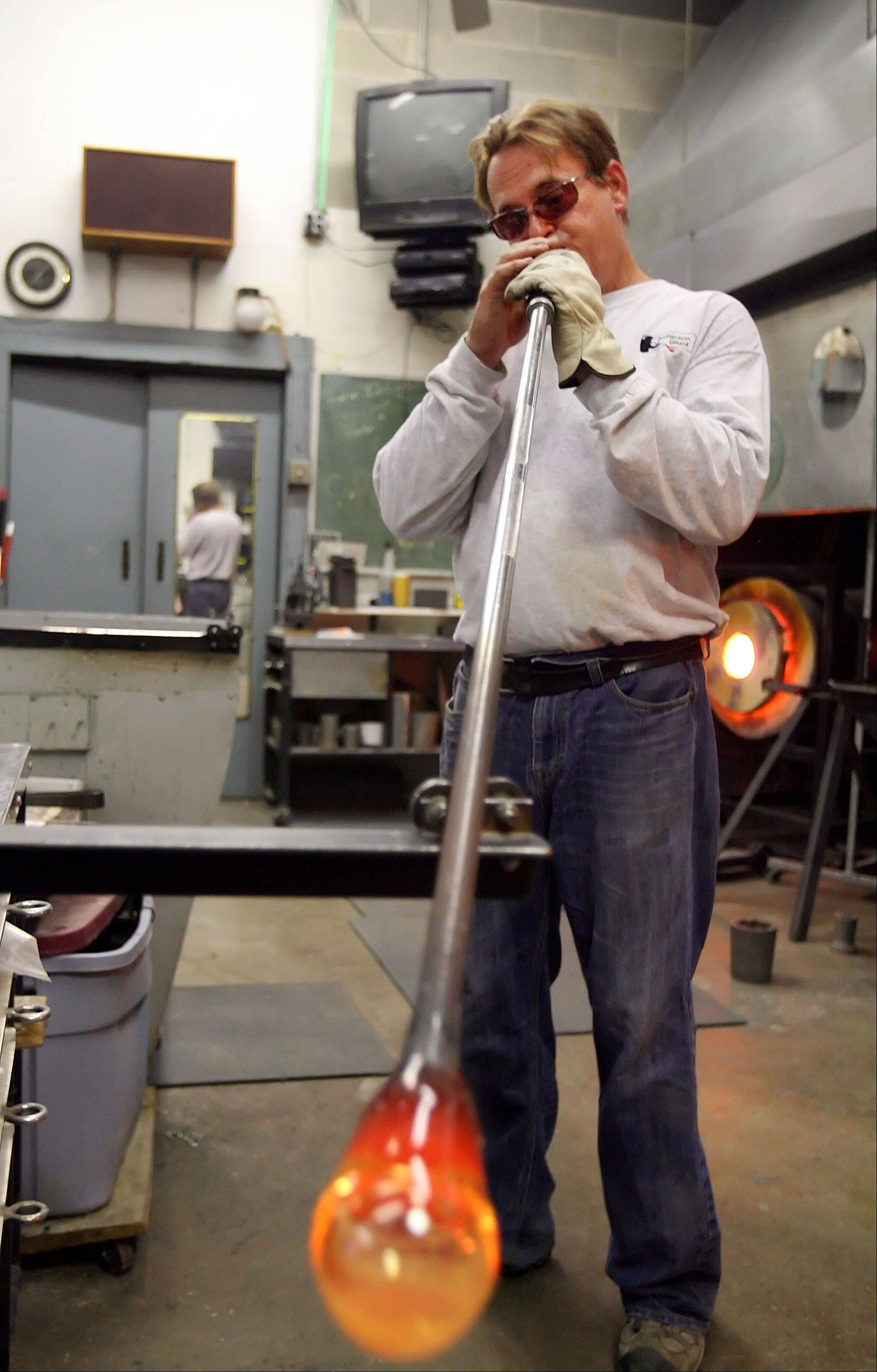 Glass artist Peter Patterson makes glass expand by blowing through a stainless steel tube.