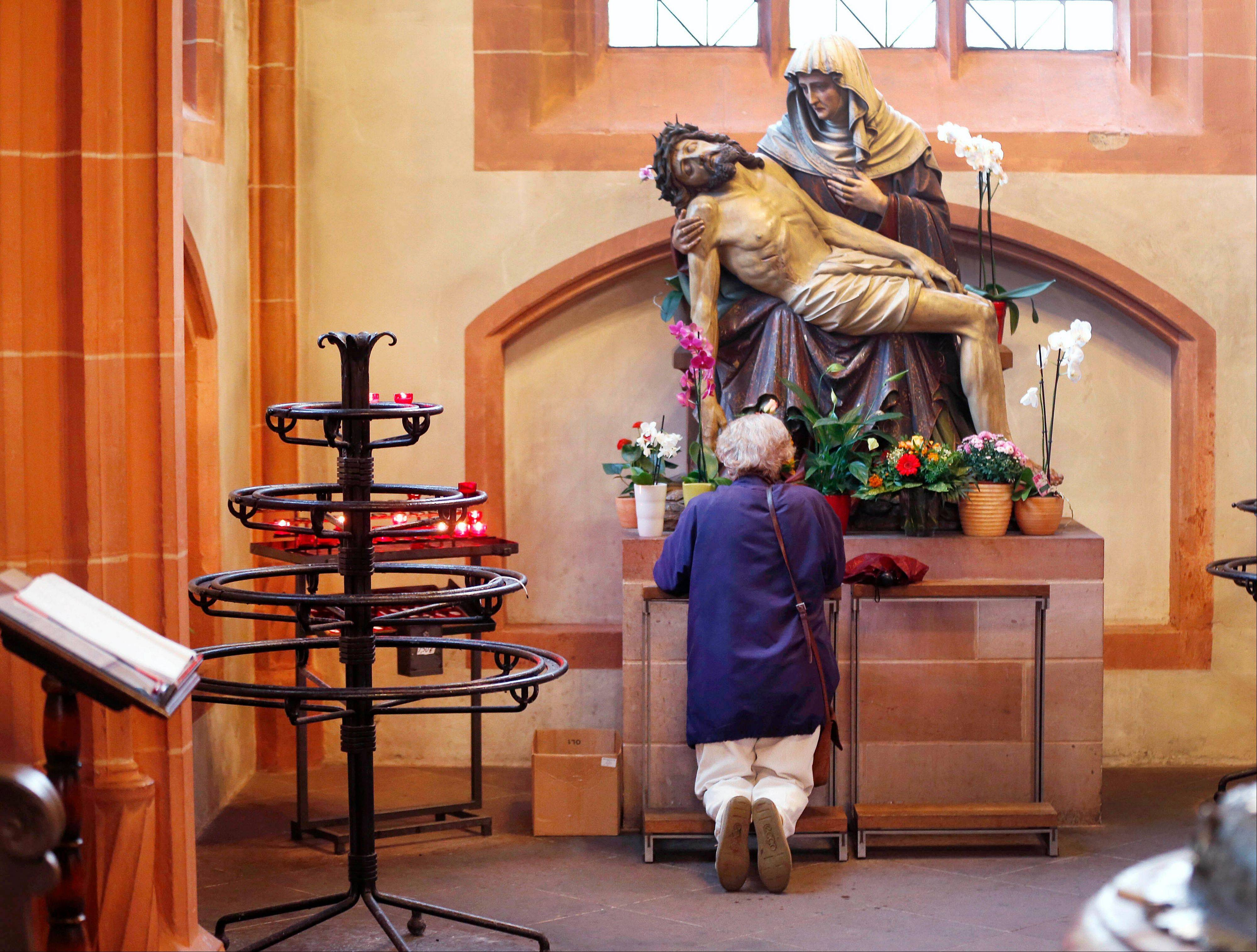 Associated PressA woman prays Thursday under a statue depicting Jesus and Mary, in the cathedral of Frankfurt, Germany.