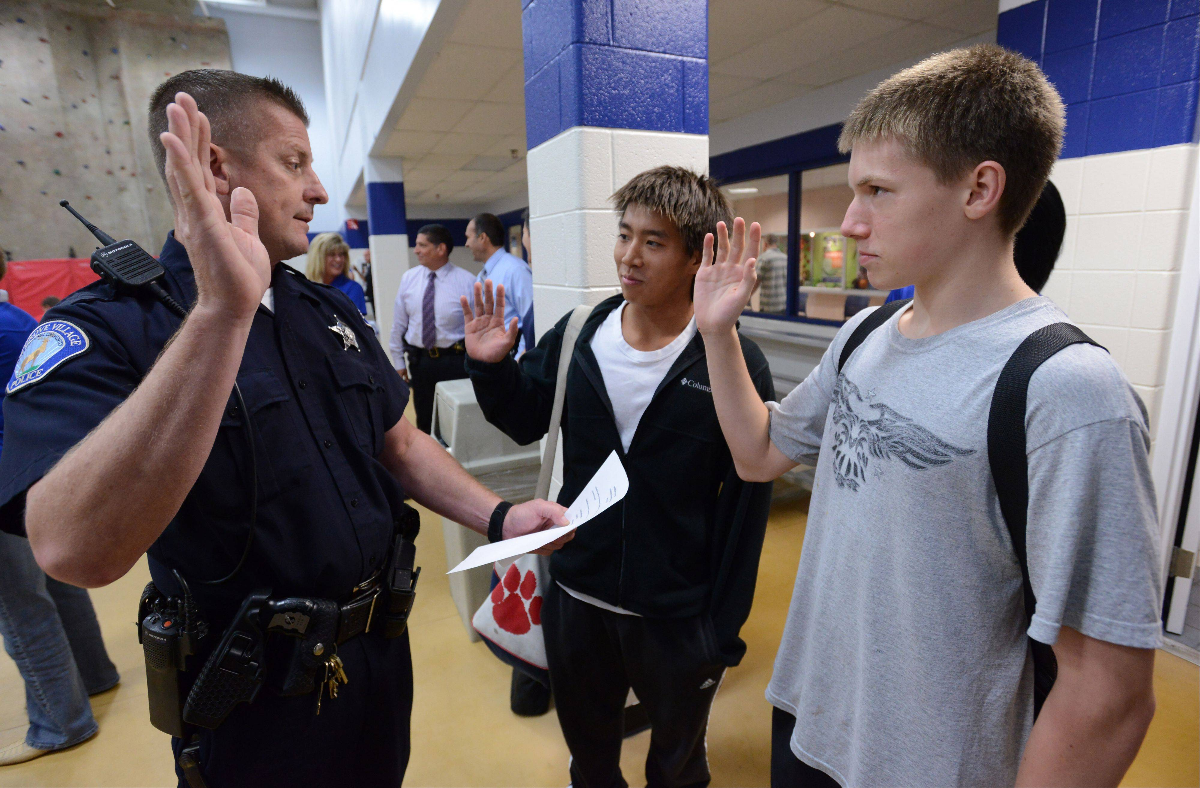 Elk Grove police officer Ed Thomas swears in Conant High School students Kazuki Morita, 17, left, and Keith Keppler, 16, at the Celebration of Character.
