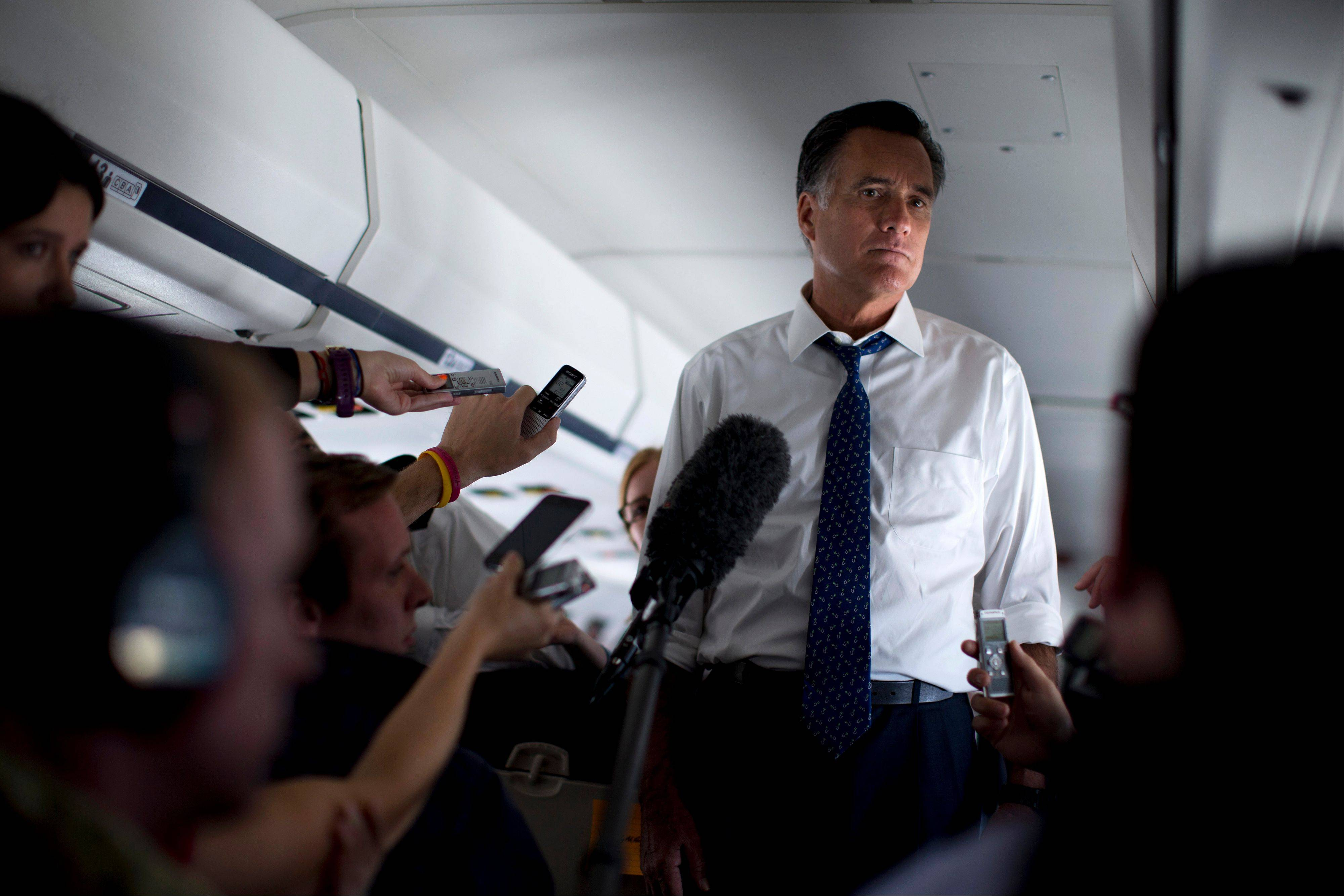 Republican presidential candidate, former Massachusetts Gov. Mitt Romney, listens to a question as he speaks with the media Friday aboard his campaign plane during a flight to Boston.