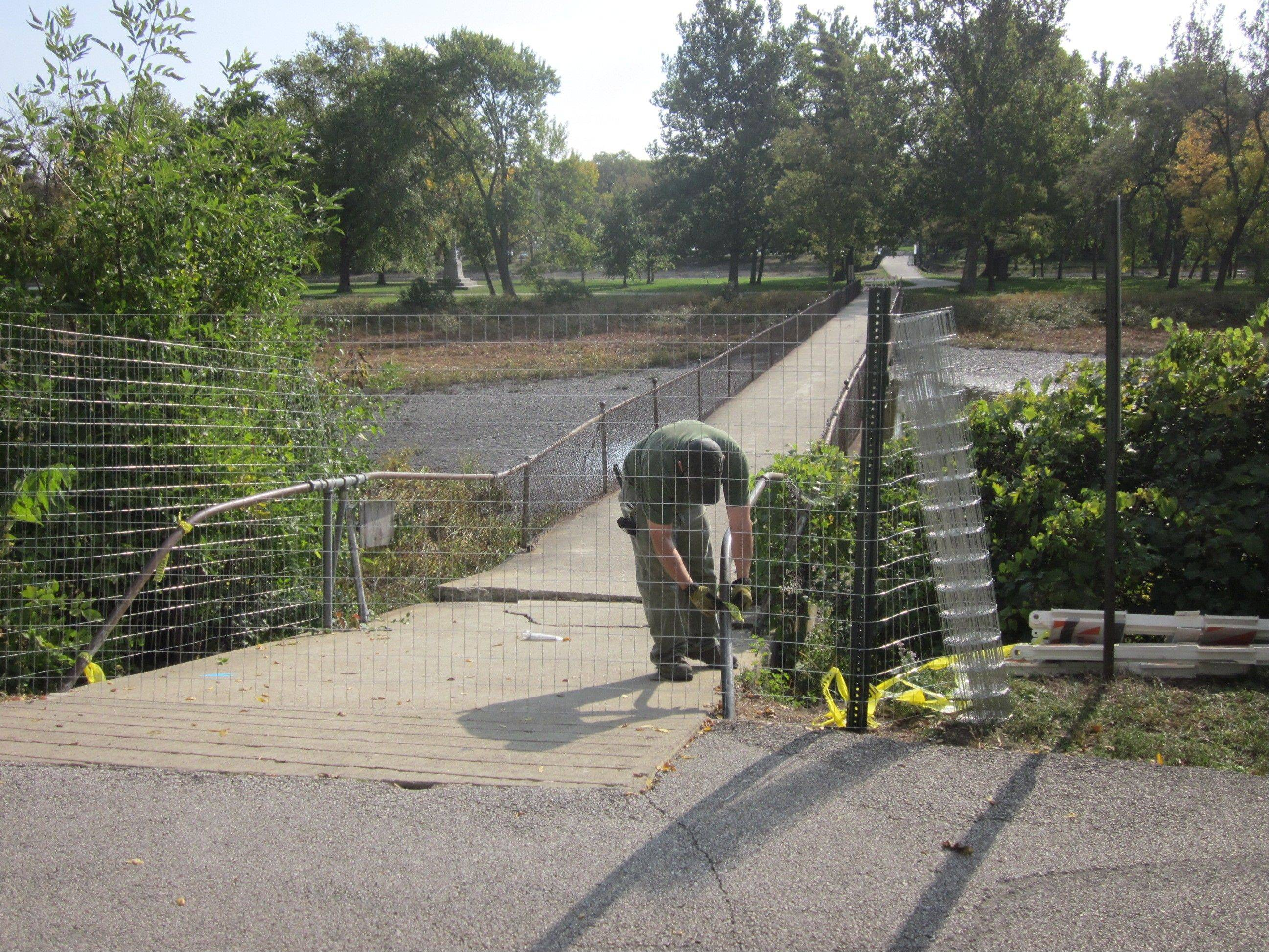 A worker barricades the western end of a bridge connecting the west bank of the Fox River to an island in Fabyan Forest Preserve Friday morning. The bridge has started collapsing at the western end.