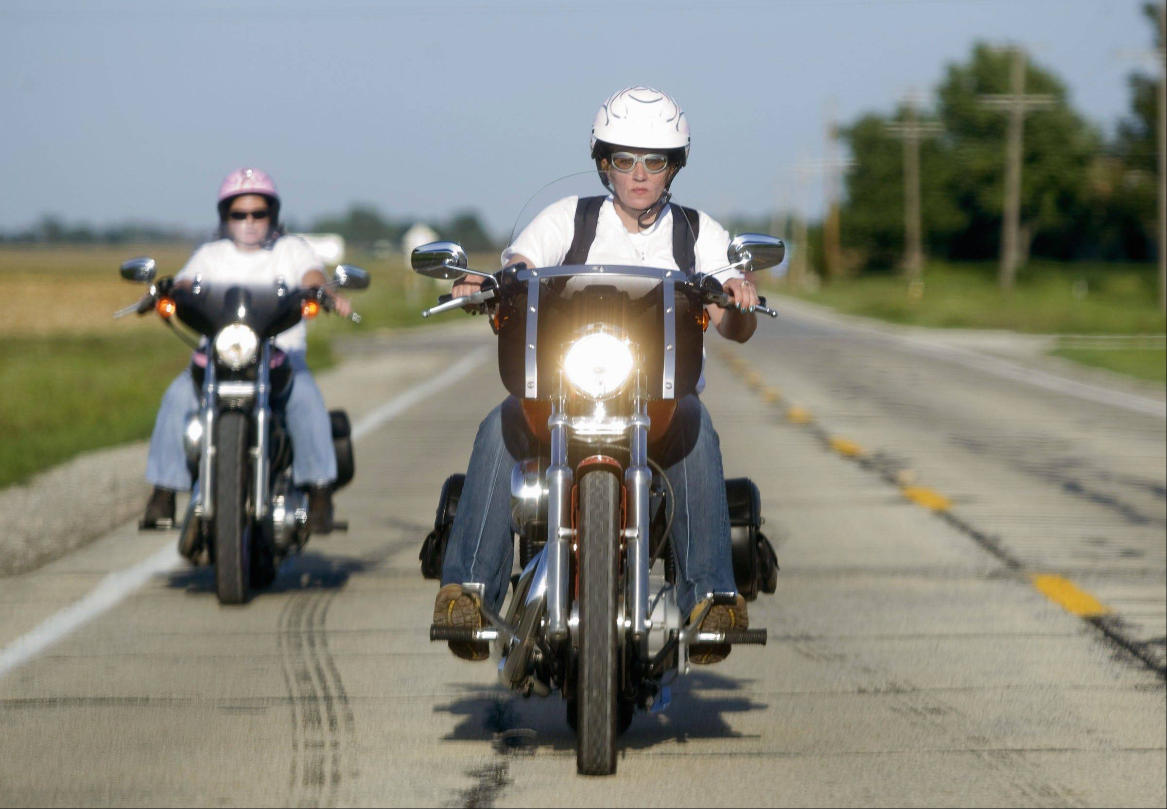 Tracie Cook, right, of Petersburg, Ill., and Tracy Cooley, of Springfield, Ill., head down Highway 36 on their motorcycles outside Niantic, Ill.