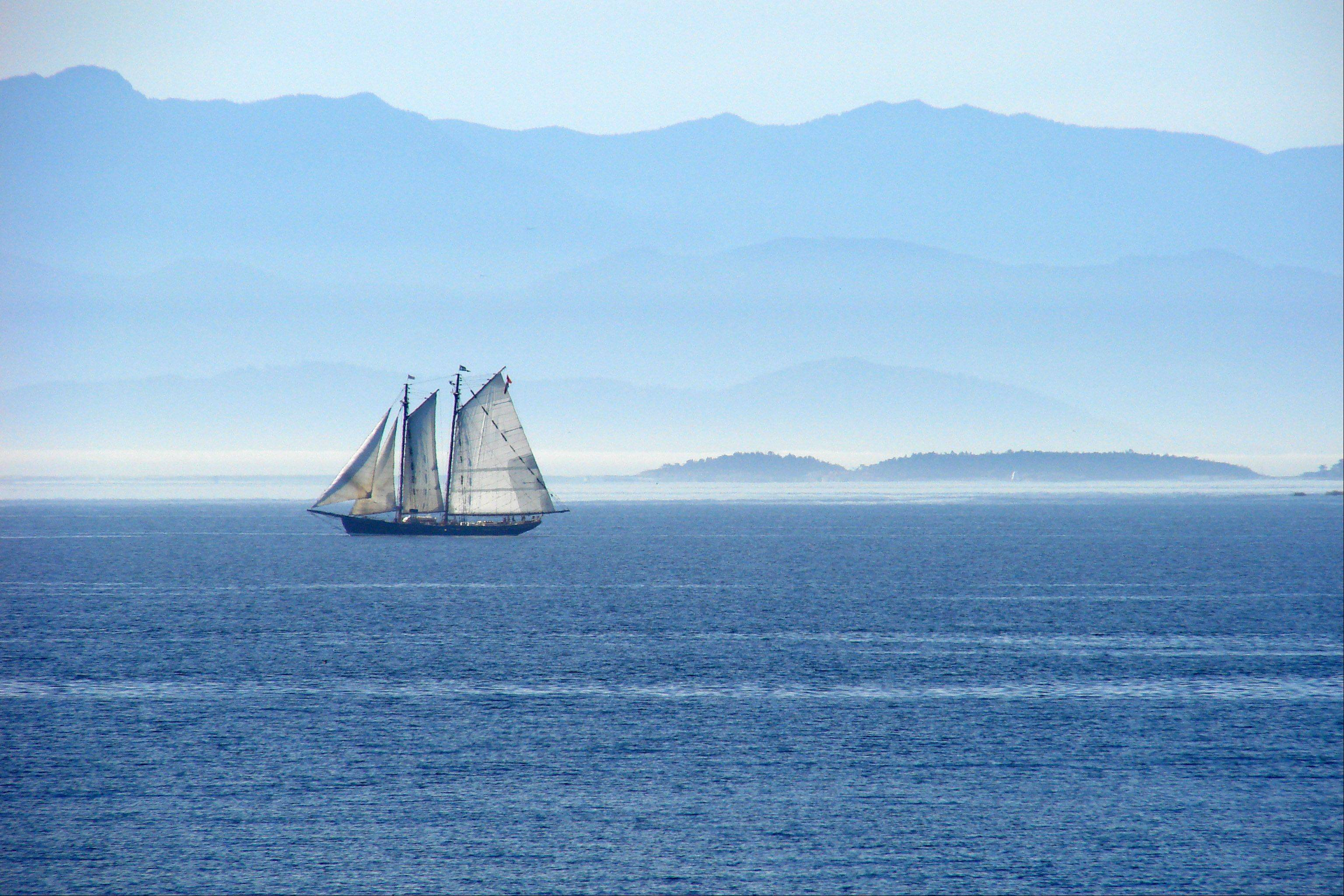 This photo of a sailing ship was taken from the Canadian Naval Station, near Victoria, BC, Canada. The opposite shore is looking in the direction of Port Angeles, Washington.