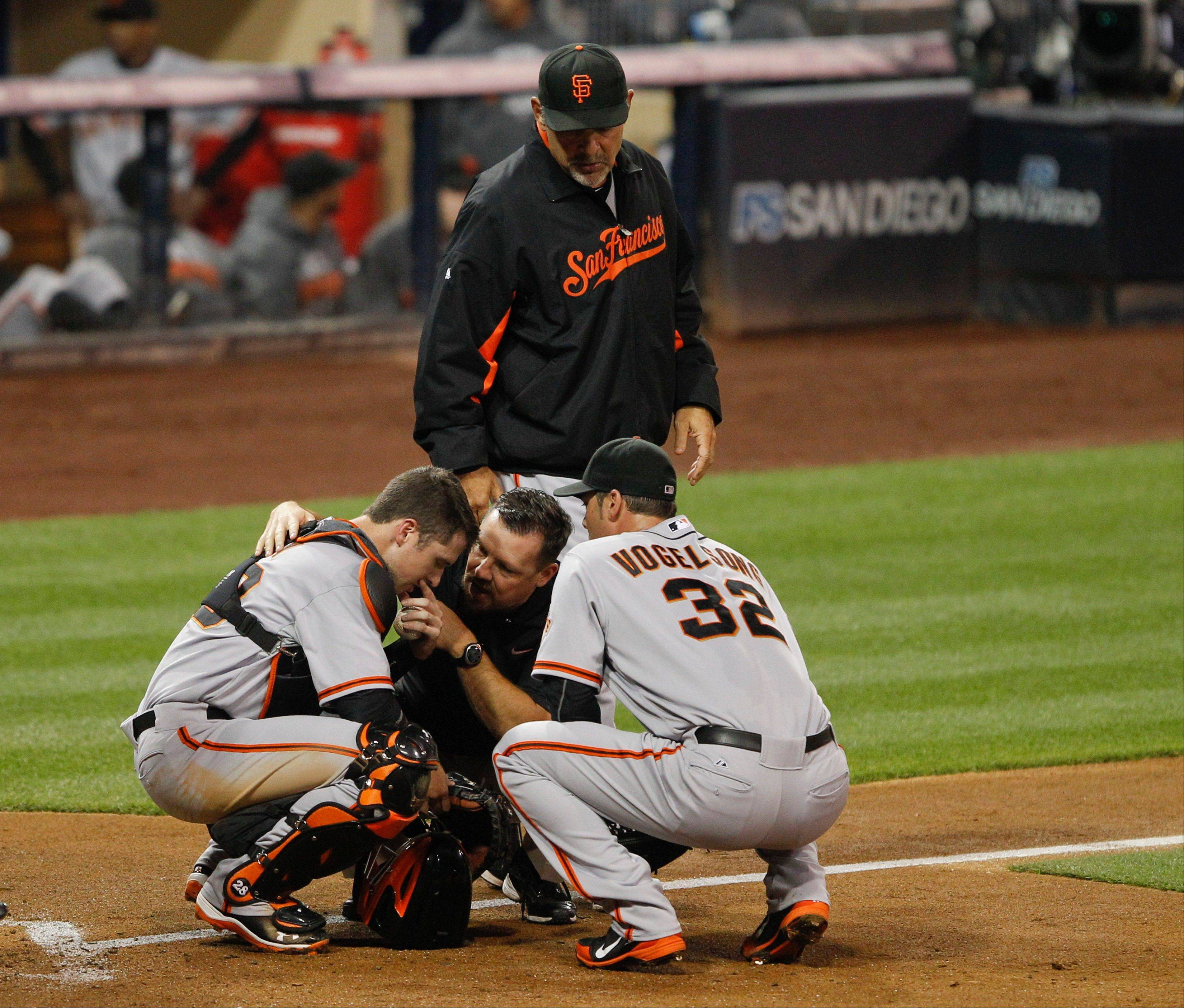 San Francisco Giants catcher Buster Posey is assisted by a trainer, pitcher Ryan Vogelsong and manager Bruce Bochy after being struck in the throat by a pitch during the second inning Friday in San Diego.