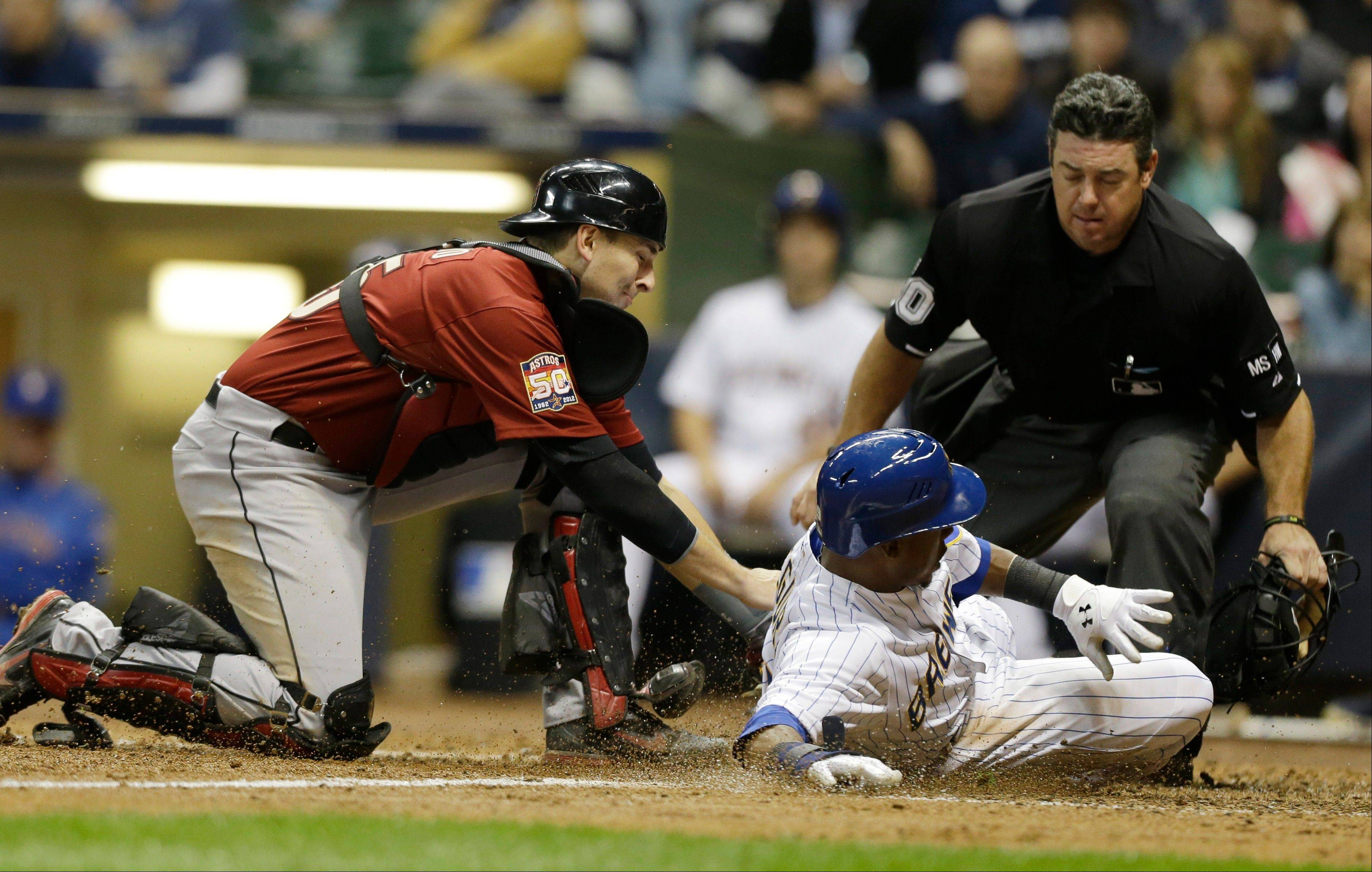 Astros catcher John Castro tags out the Brewers' Jean Segura at home plate Friday in Milwaukee. Looking on to make the call is umpire Rob Drake.