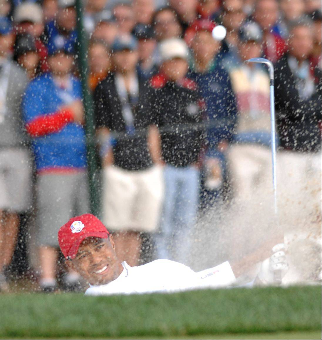 Tiger Woods blasts out of a green-side bunker on the 5th hole Friday morning during foursome play at Medinah.