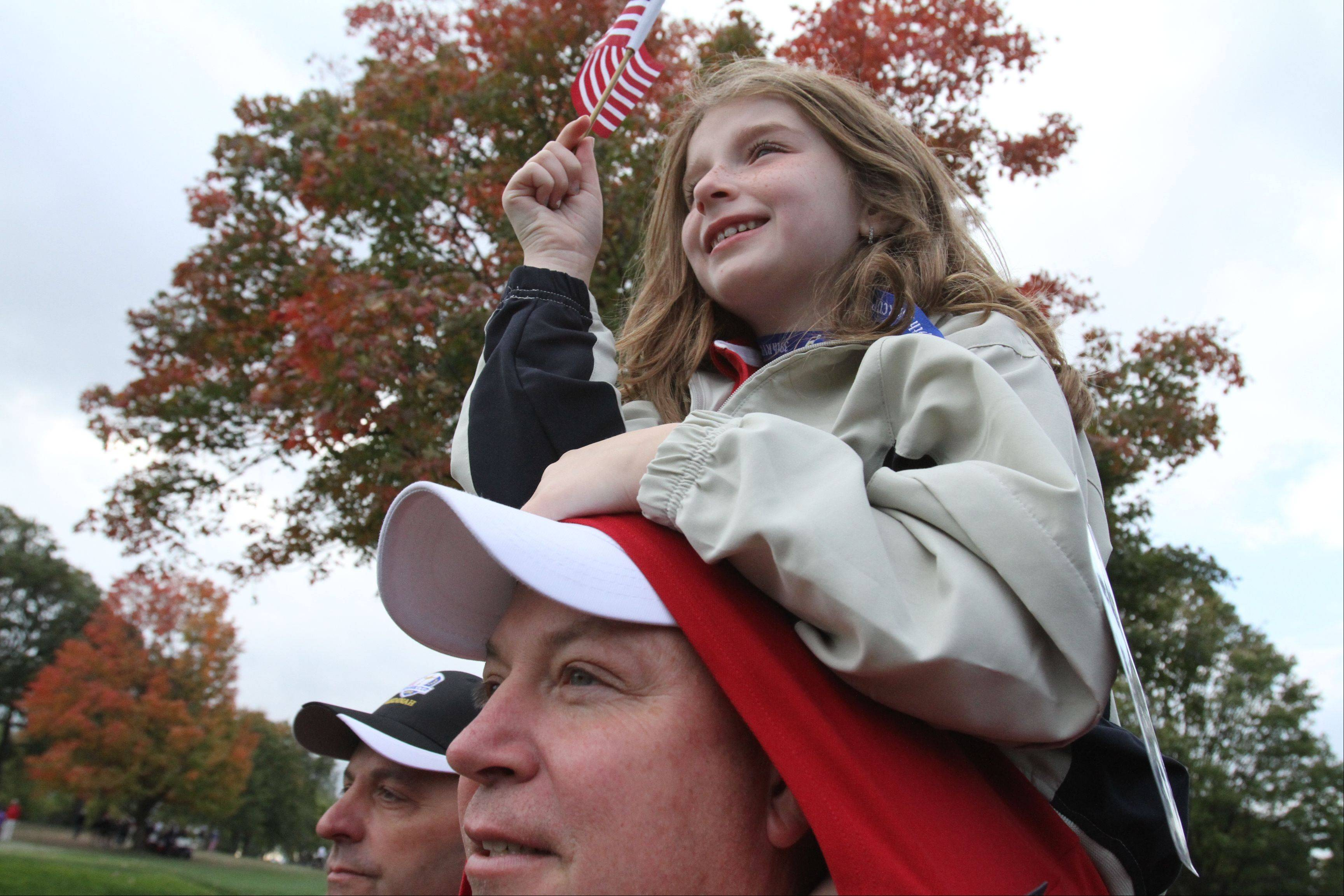 Mike Pinkowski, formerly of Glen Ellyn and now living in New York, holds his daughter Kelsey on his shoulders as they watch the Ryder Cup action Friday morning at Medinah Country Club.