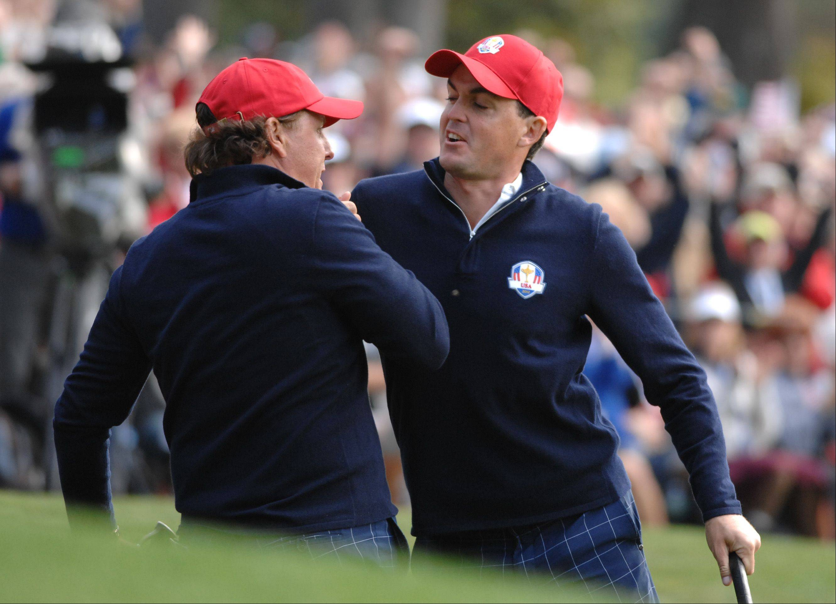 Teammates Phil Mickelson and Keegan Bradley get revved up after Mickelson made a birdie putt on 13.