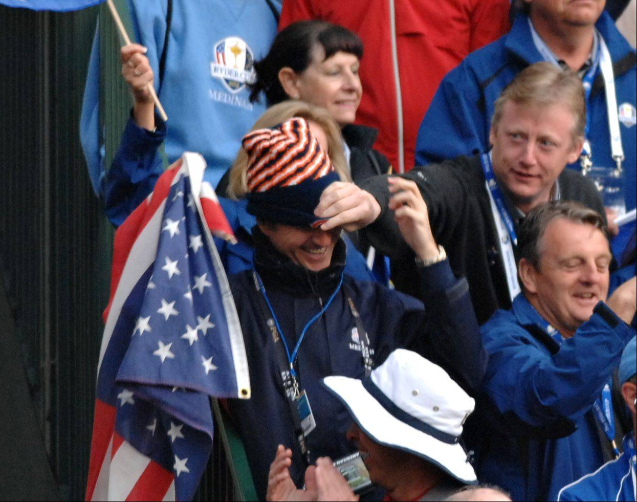A Team Europe fan pulls a hat down over the head of a Team USA fan as the rivalry gets spirited on the first tee Friday morning. The American fan was trying to get a chorus of God Bless America going, but he was outnumbered by the other fans.