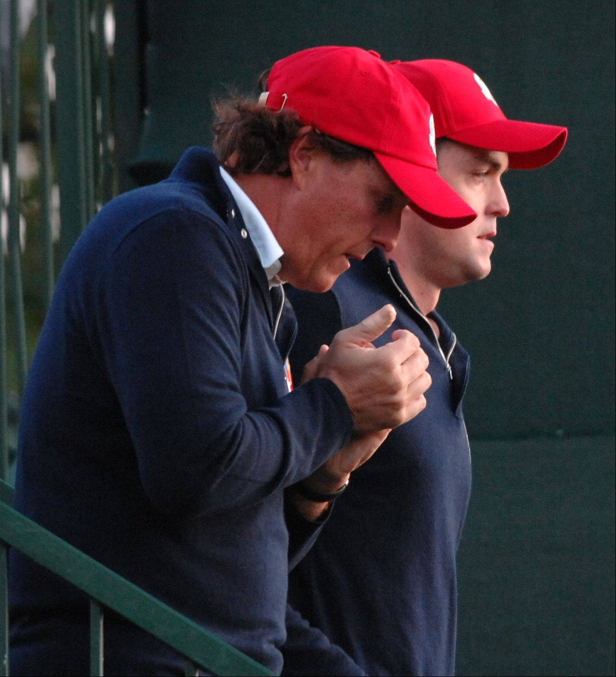 Phil Mickelson warms his hands on a chilly fall morning at Medinah Country Club as he walks to the first tee with teammate Keegan Bradley.