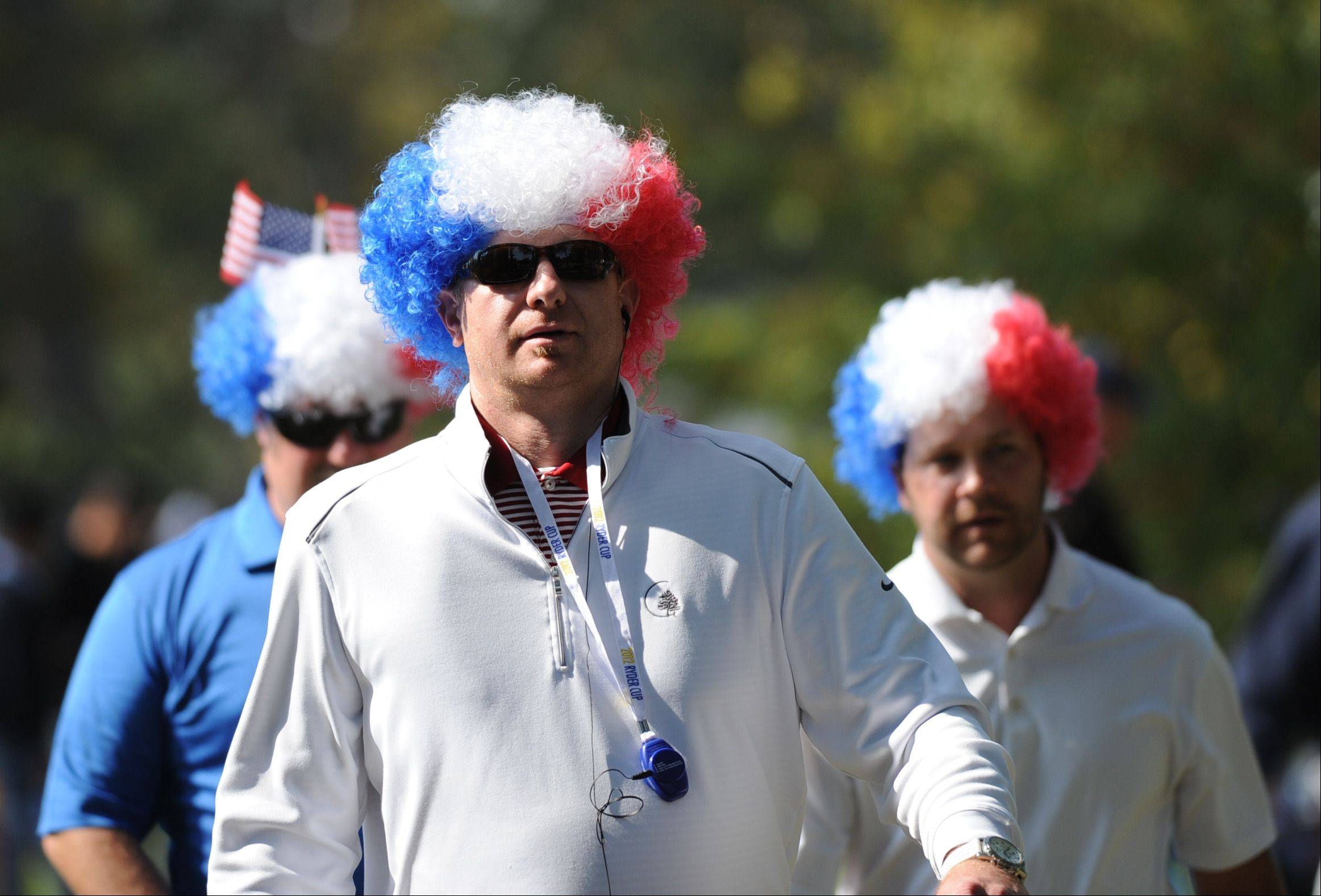 A trio of colorful golf fans make their way through the grounds at Medinah Friday.