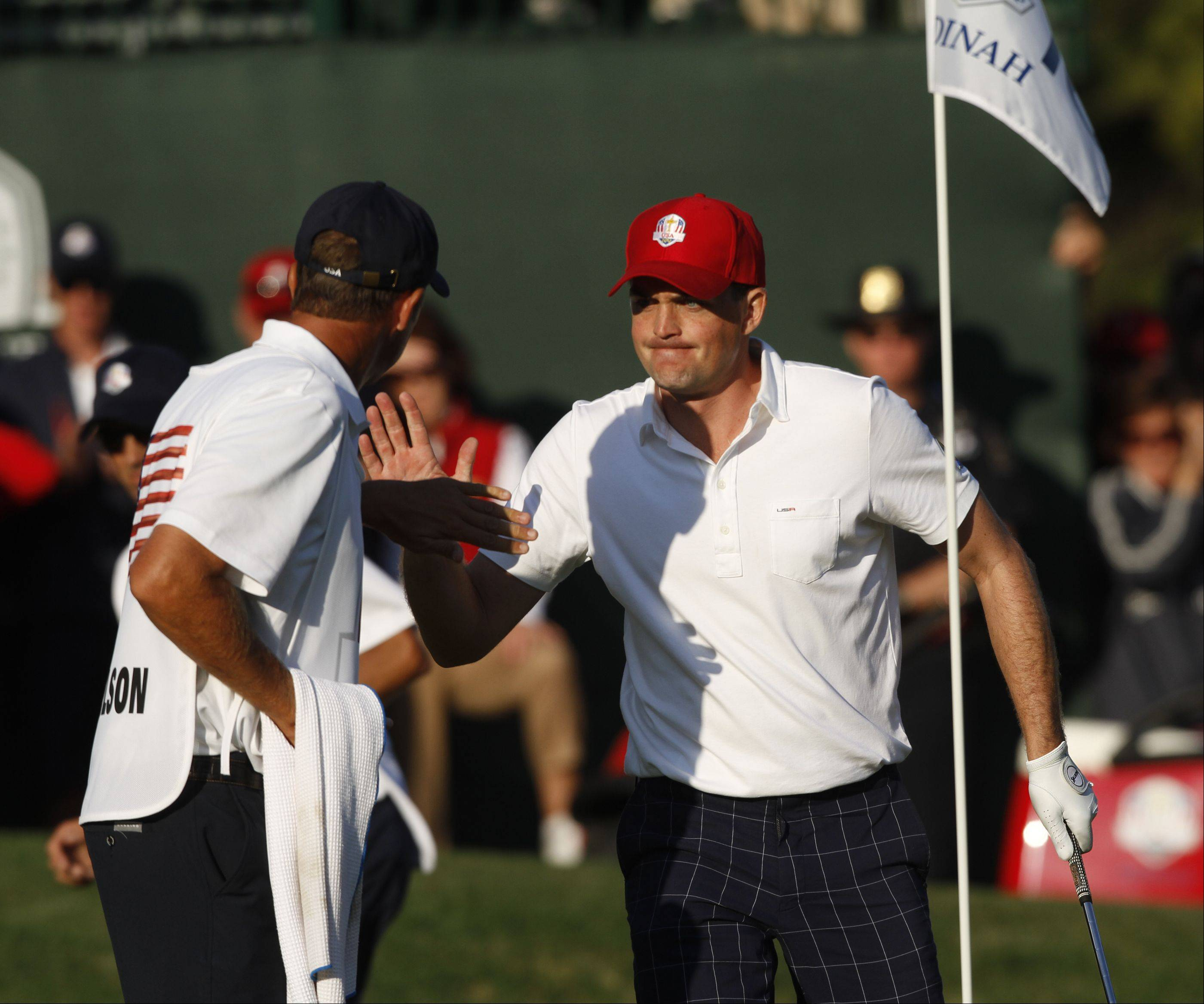 Keegan Bradley high fives his caddy after chipping close to the cup on the 16th hole Friday afternoon at the 2012 Ryder Cup at Medinah Country Club.