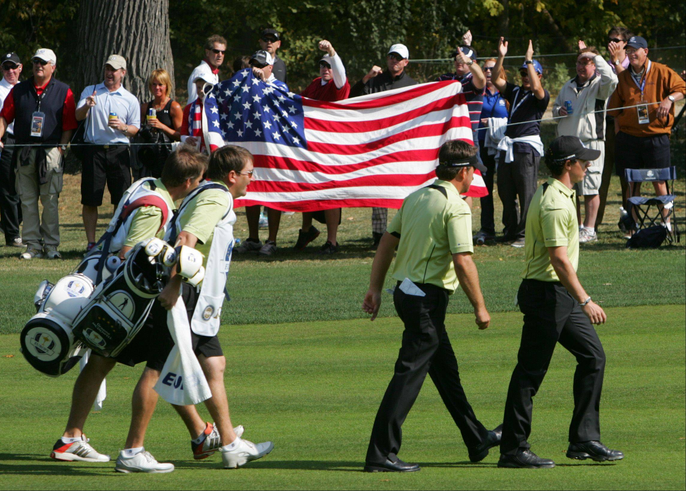 Team Europe teammates Graeme McDowell and Rory McIlroy stroll a fairway flanked by American fans Friday afternoon.
