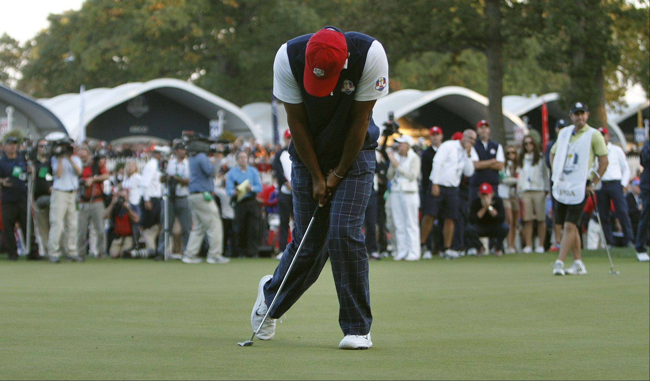 Tiger Woods collapses after missing a birdie putt on 18 during fourball matches Friday at Medinah Country Club.