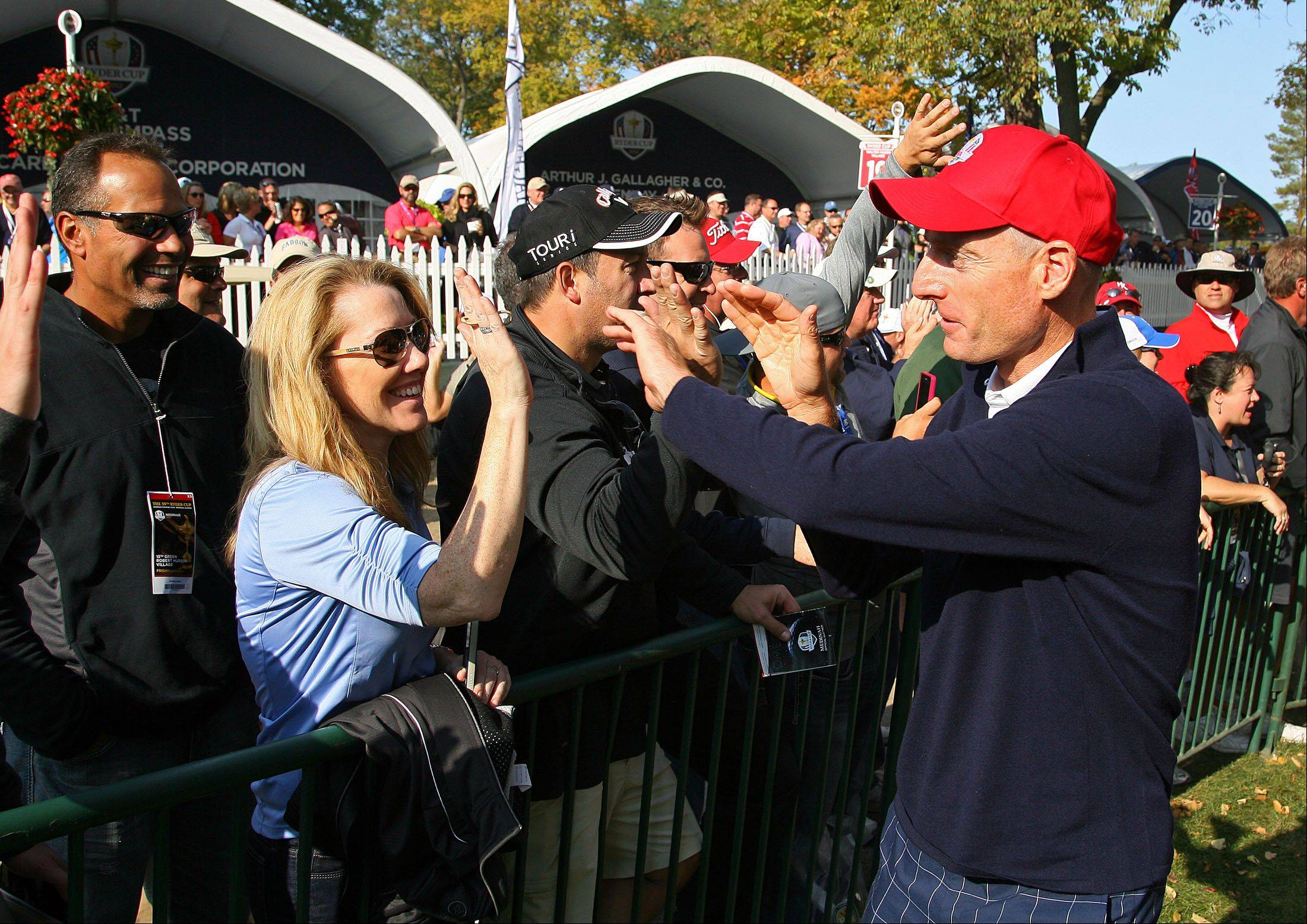 Jim Furyk high fives fans as he heads to the 14th tee following Bubba Watson and Webb Simpson during fourball matches Friday at Medinah Country Club.