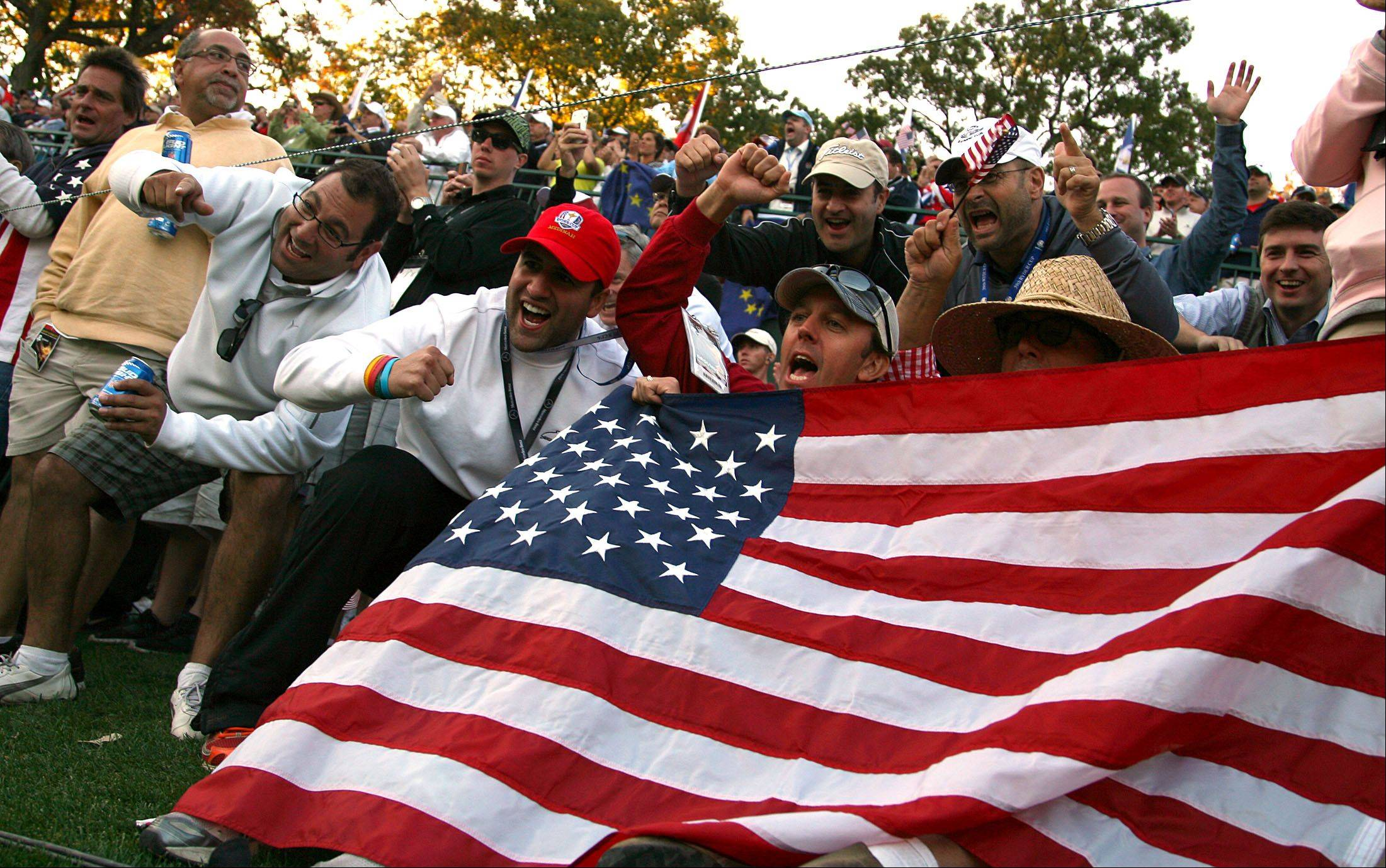 Fans cheer on Tiger Woods at the 17th hole during fourball matches Friday at Medinah Country Club.