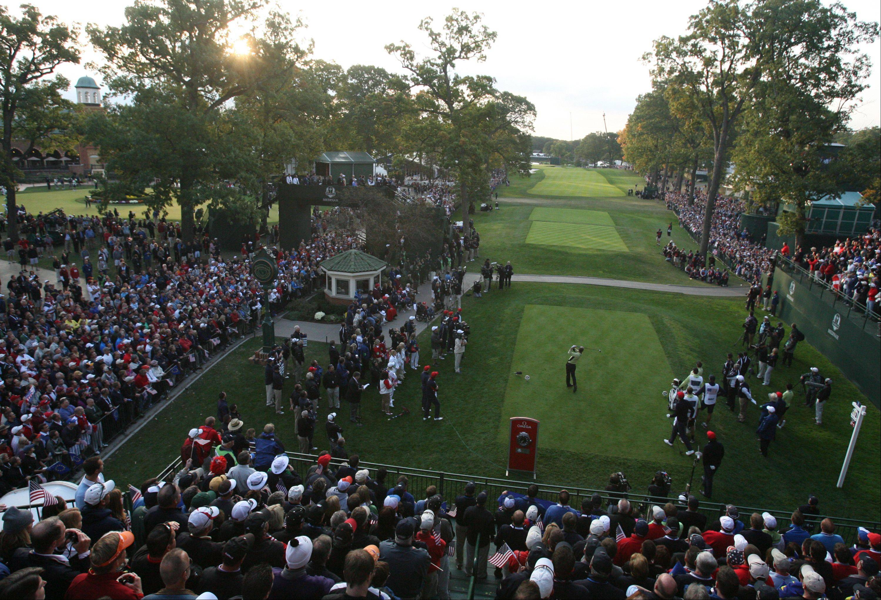 Luke Donald of Team Europe tees off as the sun rises through the trees at Medinah Country Club.