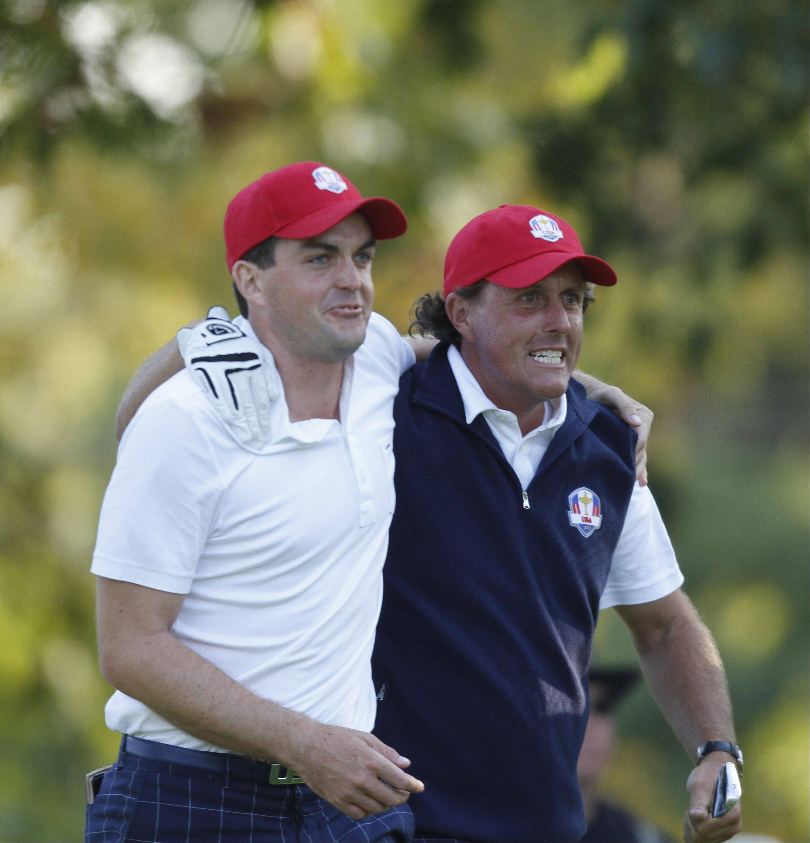 Keegan Bradley, left, and Phil Mickelson congratulate each other after Mickelson's drive on the 17th hole land just feet from the cup. That drive clinched the match for their round and gave the US team another point Friday afternoon at the 2012 Ryder Cup at Medinah Country Club.