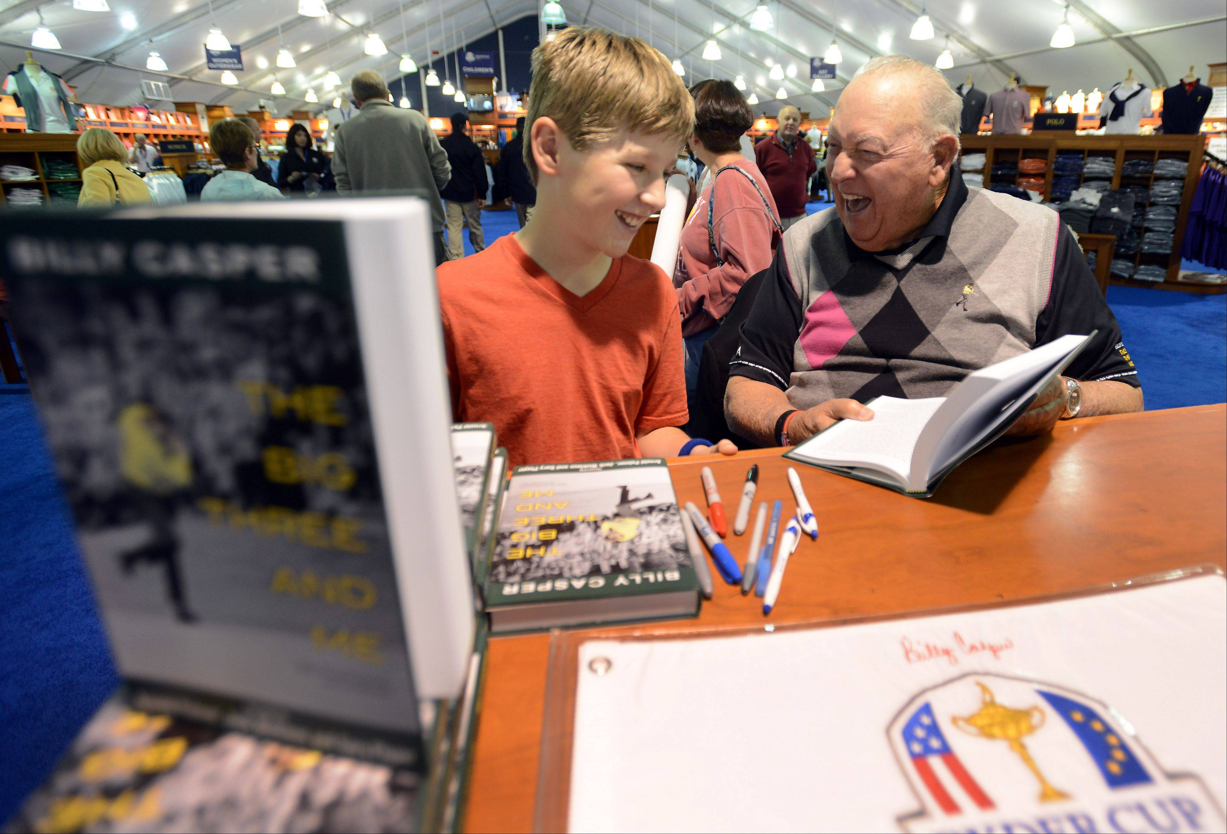 Hunter Wark,11, of Glen Ellyn shares a laugh with World Golf Hall of Famer Billy Casper as he signs his book for him at the Ryder Cup golf pro shop on Sunday. Fans have flocked to the merchandise tent since it opened.